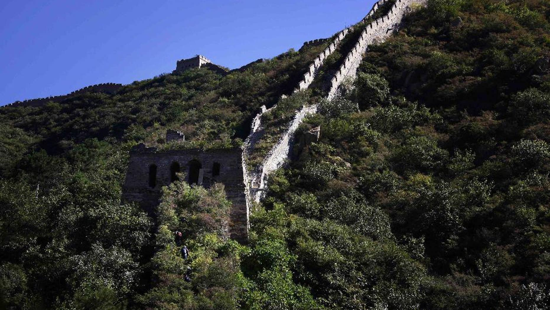 Chinese hikers make their way up an overgrown, hidden section of the Great Wall of China located near Xiang Shui Hu village.