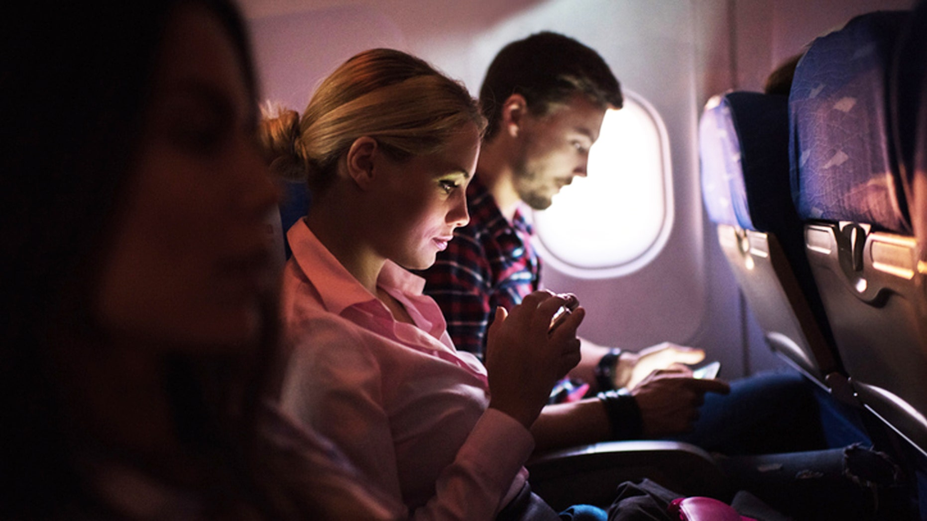 People traveling by airplane. Focus is on young woman text messaging.