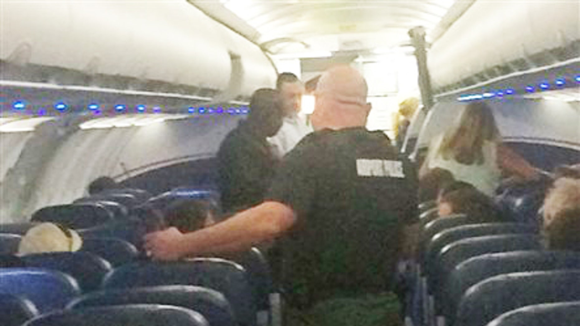This Tuesday, Nov. 3, 2015, photo provided shows airport police aboard a plane after an emergency landing at Eisenhower National Airport in Wichita, Kan. The U.S. Attorney's Office says a disruptive passenger who forced the diversion of the American Airlines flight from Phoenix to New York will face federal charges.