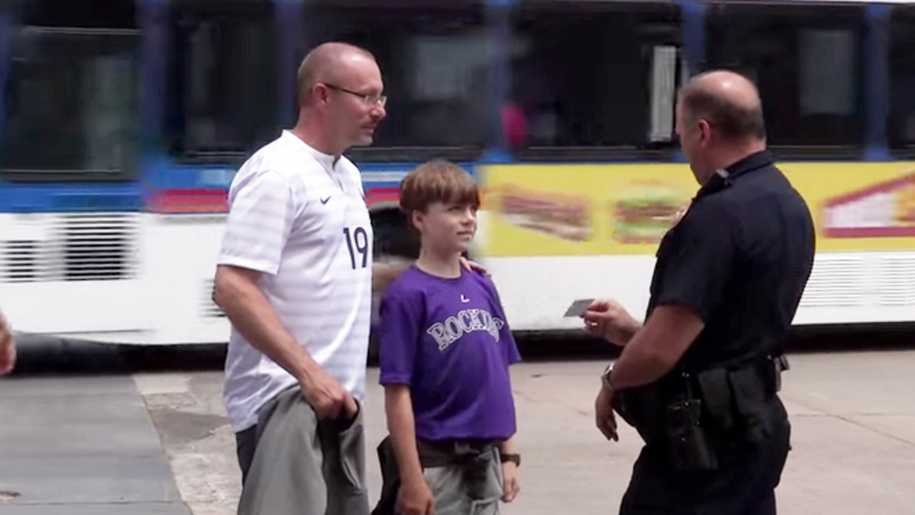 A police officer hands out a pizza card to well behaved duo.