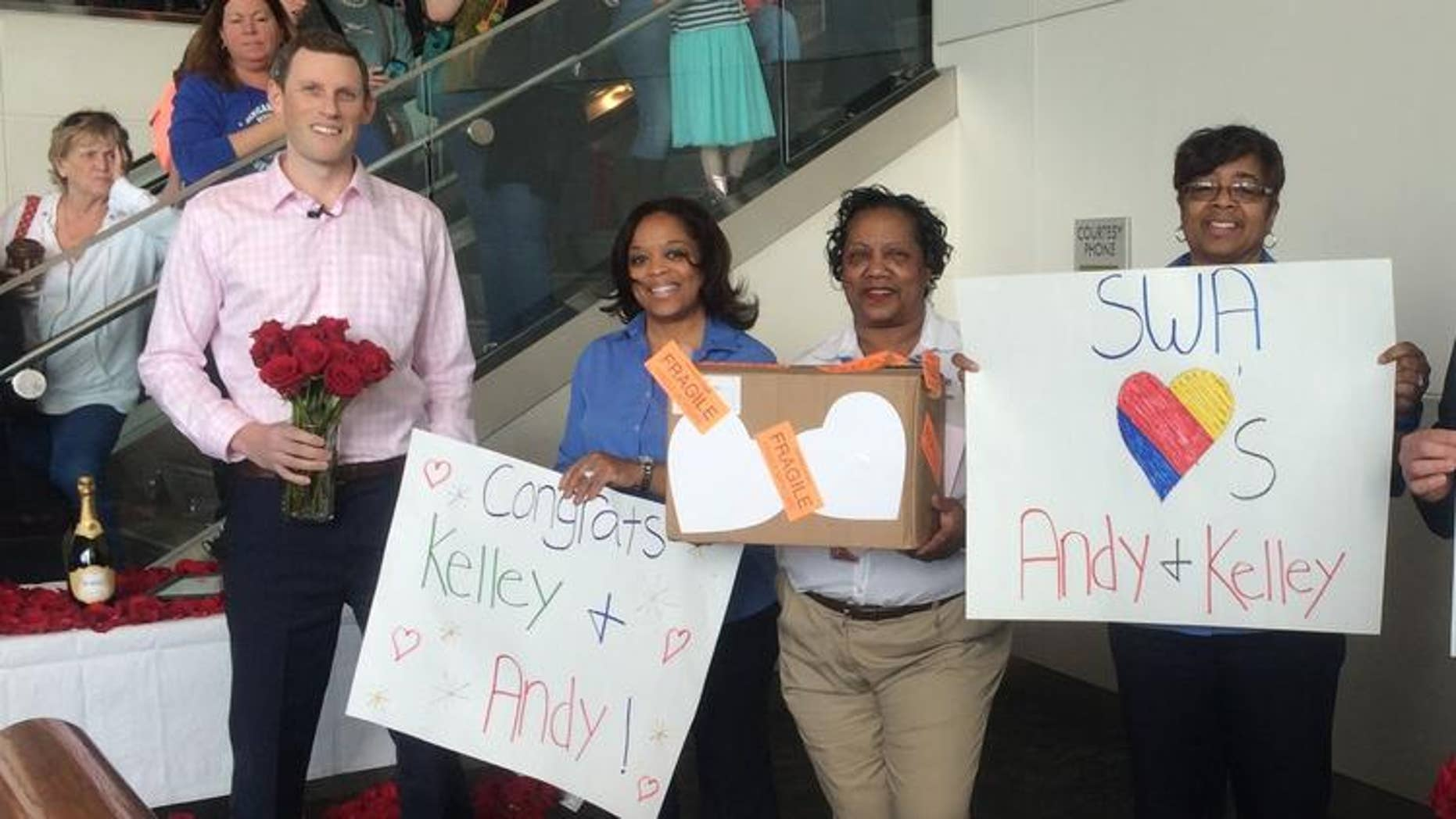 Andy McIlvaine, far left, waits with Southwest Airlines employees and passengers wait for his fiancee to arrive at BWI airport.
