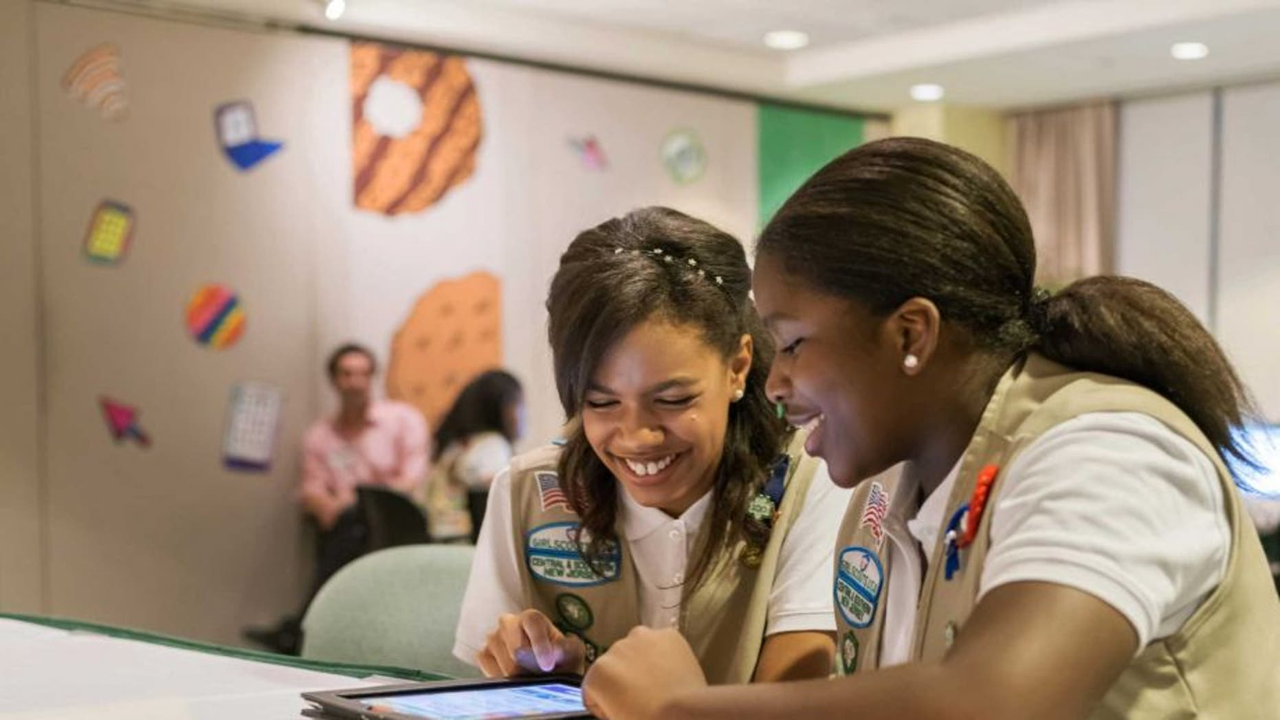 In this undated photo released by Girl Scouts of the USAGirl Scouts, Bria and Shirell practice selling cookies on one of two new digital platforms. It's the first time Girls Scouts of the USA has allowed sale of cookies using a mobile app and personalized websites. The Digital Cookie program is intended to enhance, not replace, traditional use of paper spreadsheets.
