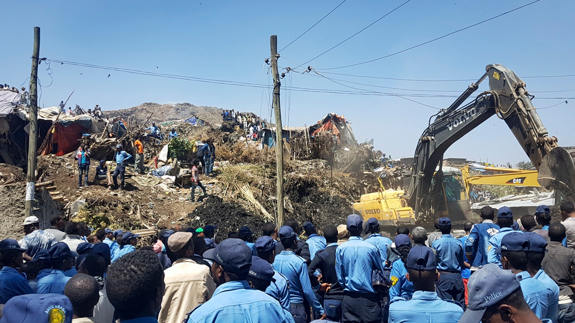 Police officers secure the perimeter at the scene of a garbage landslide, as excavators aid rescue efforts, on the outskirts of the capital Addis Ababa, Ethiopia Sunday, March 12, 2017.