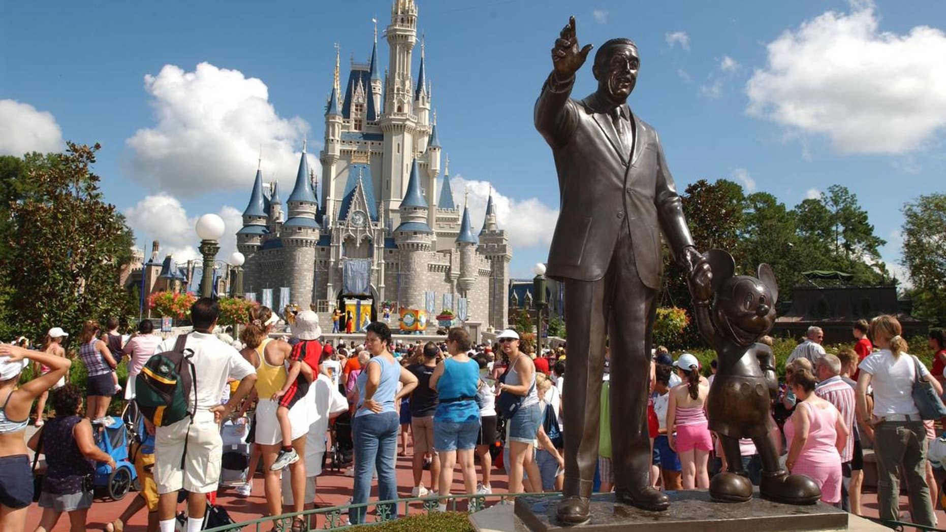 Tourists stop by Cinderella's Castle  performance at Walt Disney World's Magic Kingdom in Lake Buena Vista, Fla.