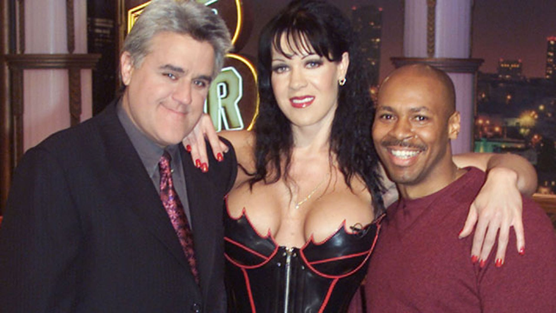 """World Wrestling Federation wrestler Chyna poses with talk show host Jay Leno and band leader Kevin Eubanks on the set of """"The Tonight Show."""" (Reuters)"""