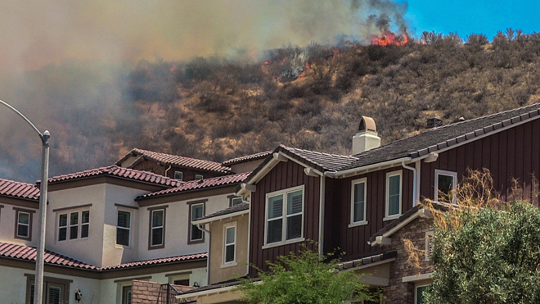 In this July 9, 2016 photo, flames line a hillside behind homes on Old Stone Way as the Sage Fire roared through the Stevenson Ranch area of Santa Clarita, Calif. A fast-moving brush fire north of Los Angeles has sent about 2,000 people fleeing from their homes.  (Austin Dave/The Santa Clarita Valley Signal via AP)