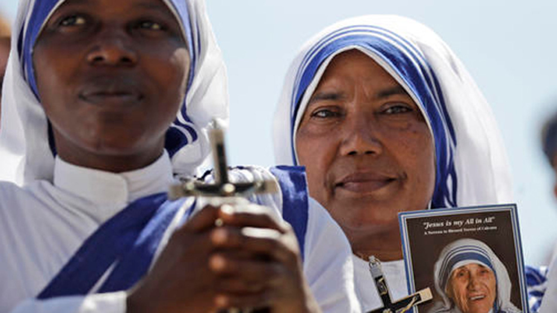 Missionaries of Charity nuns holds a photo of Mother Teresa in St. Peter's Square at the Vatican during a jubilee audience for workers and volunteers of mercy led by Pope Francis, Saturday, Sept. 3, 2016. The square hosts a ceremony Sunday expected to draw hundreds of thousands of admirers of Mother Teresa, a nun who before her death in 1997, cared for the destitute who were dying in the streets of India. (AP Photo/Alessandra Tarantino)