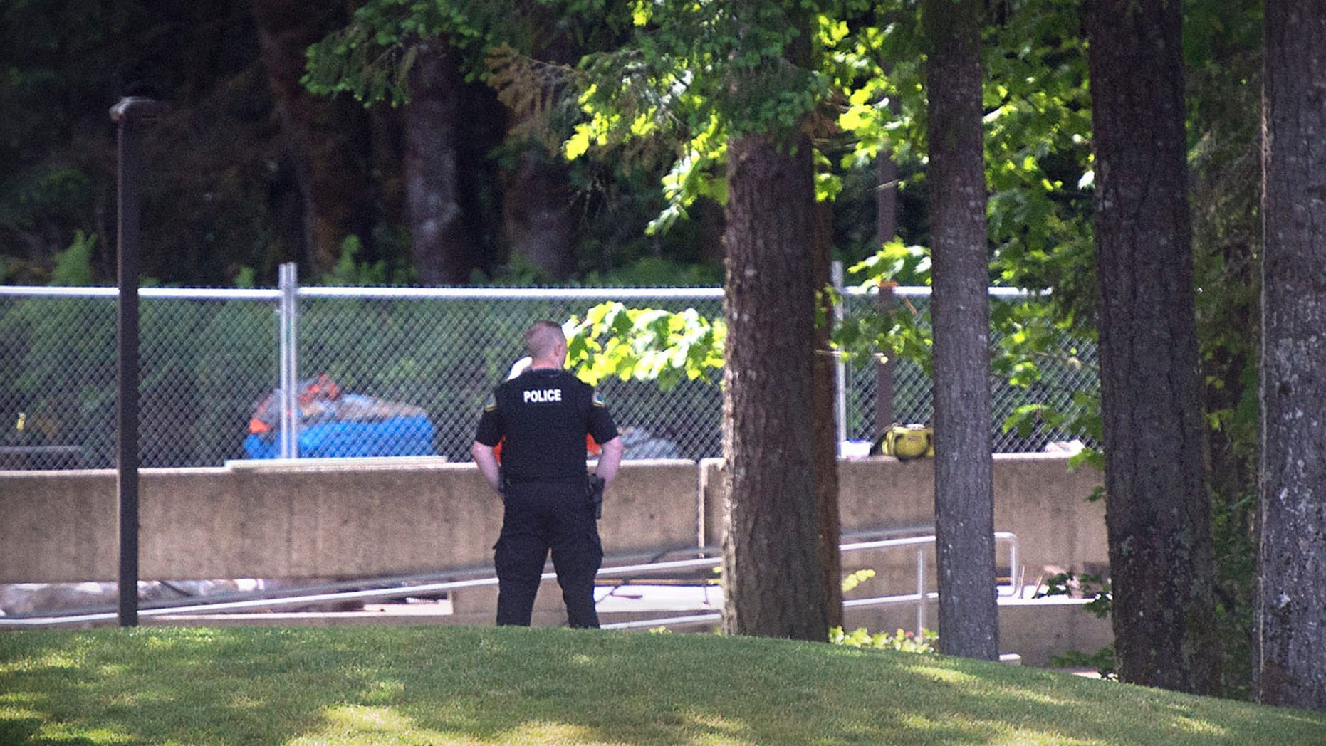 """An Evergreen State College police officers keeps watch over campus as student evacuate following a """"direct threat"""" on Thursday, June 1, 2017.  The announcement posted on the school's website Thursday asked everyone to leave the Olympia campus or return to residence halls for further instructions. The post did not provide other details. (Tony Overman /The Olympian via AP)"""