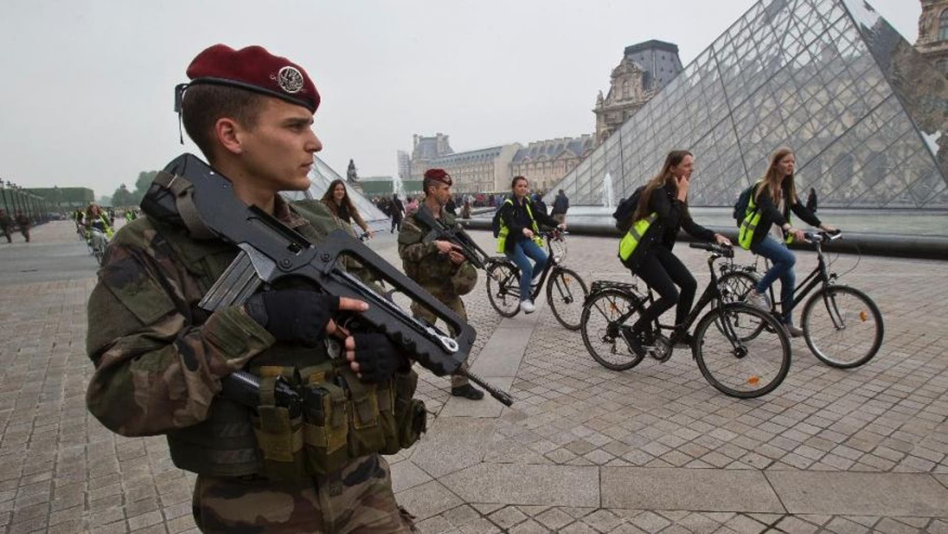 A French soldier staff sergeant Baudouin guards the iconic entrance to the Louvre museum in Paris, Friday, May 13, 2016.