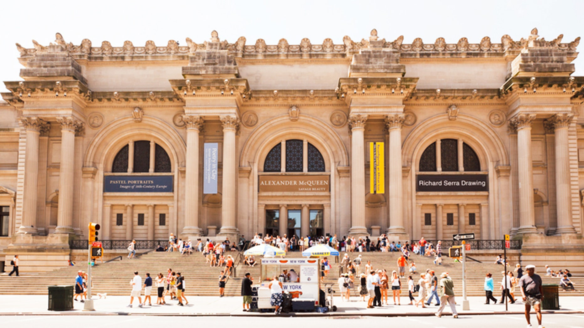 """""""New York, New York, USA - July 10, 2011: The recently renovated exterior of the Metropolitan Museum of Art in New York City. Visited by millions of people each year, this world renowned museum is located on 5th avenue between 80th and 84th streets. People can be seen entering and exiting through the main entrance as well as relaxing on the large staircase. A food cart provides refreshments for pedestrians."""""""