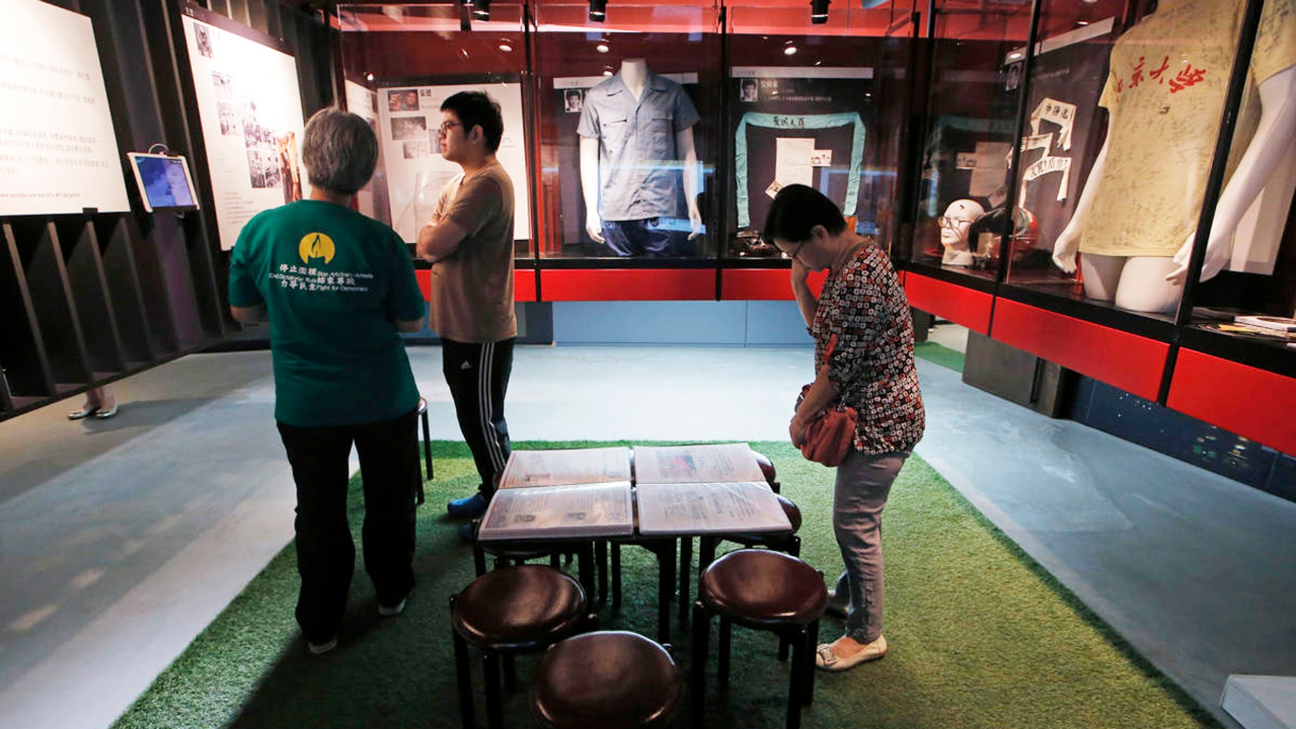 Visitors look at the exhibits in the June 4th Museum in Hong Kong, Friday, April 15, 2016. The operators of the world's only museum chronicling the Chinese government's brutal 1989 crackdown on student protesters in Beijing's Tiananmen Square say it faces closure because of a legal dispute. (AP Photo/Kin Cheung)
