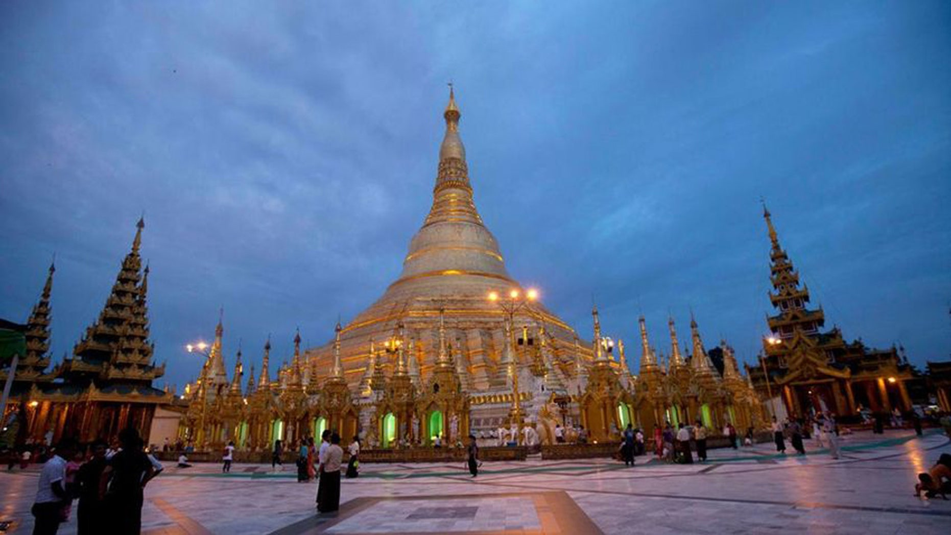 Buddhist devotees visit Myanmar's famous Shwedagon Pagoda as its illuminated in Yangon, Myanmar on Aug. 13, 2014.
