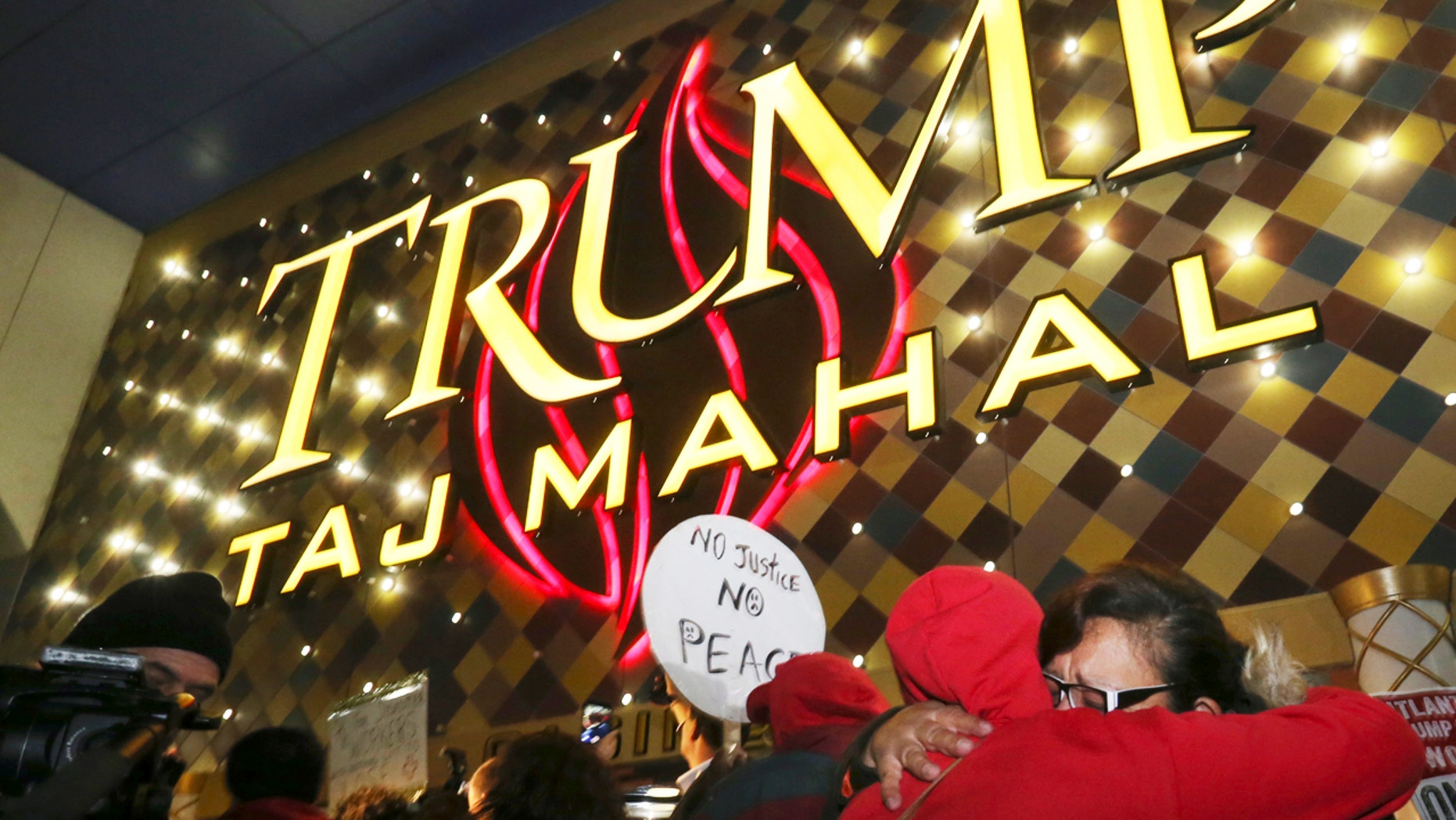 Former employees hug early in the morning outside the closing Trump Taj Mahal, Monday, Oct. 10, 2016, in Atlantic City, N.J. Nearly 3,000 workers were laid off amid the hotel's closure.