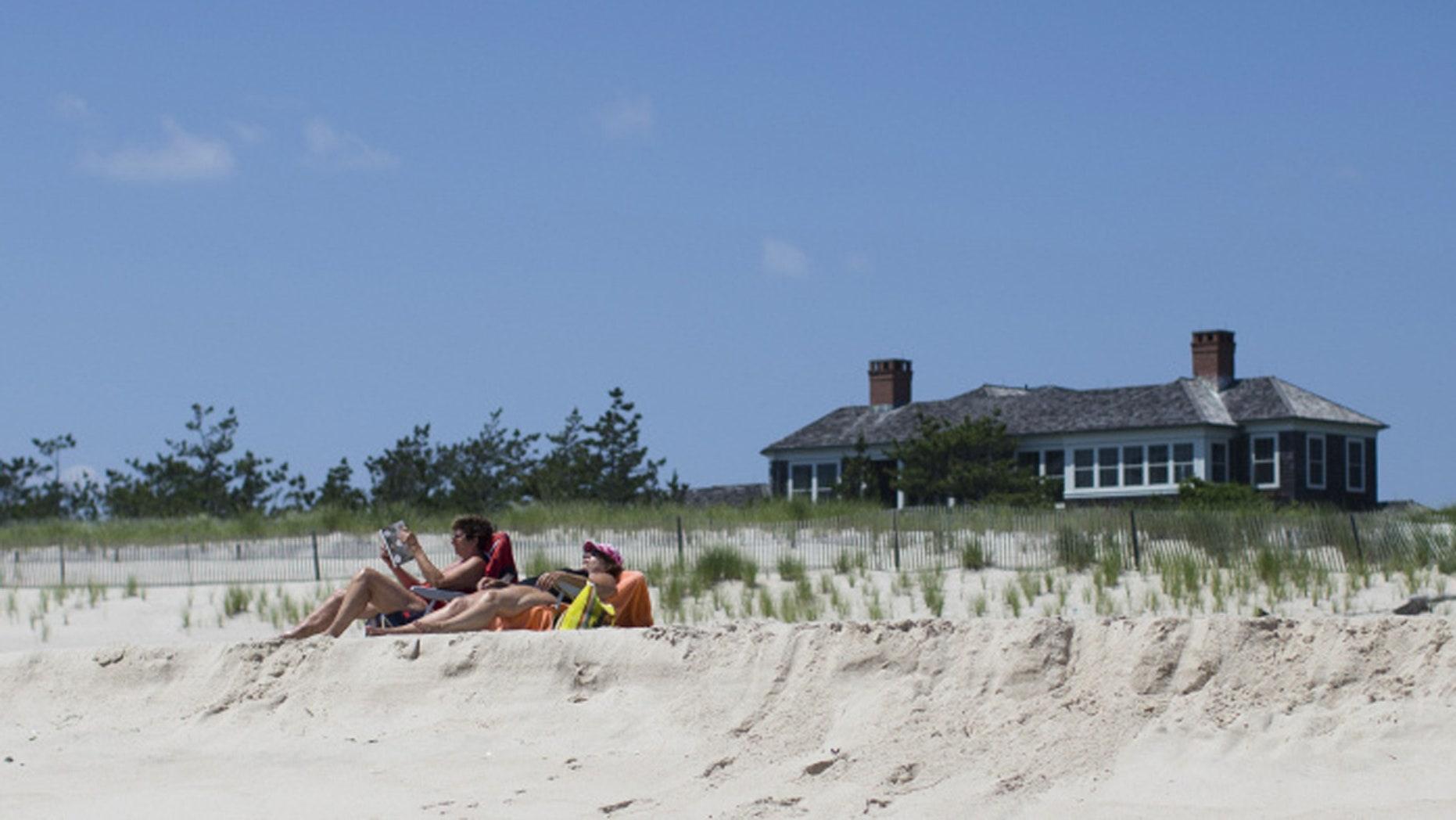 Beachgoers relax near a beachfront property in Southampton, N.Y.