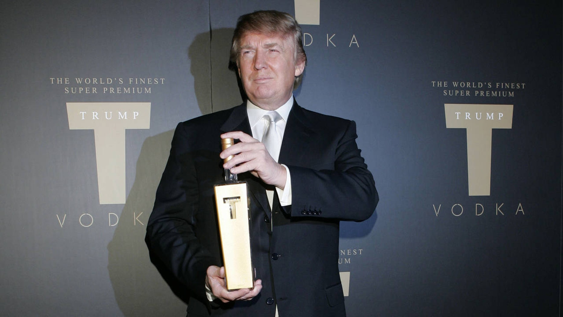 Donald Trump poses with a bottle of liquor from his now defunct vodka line.