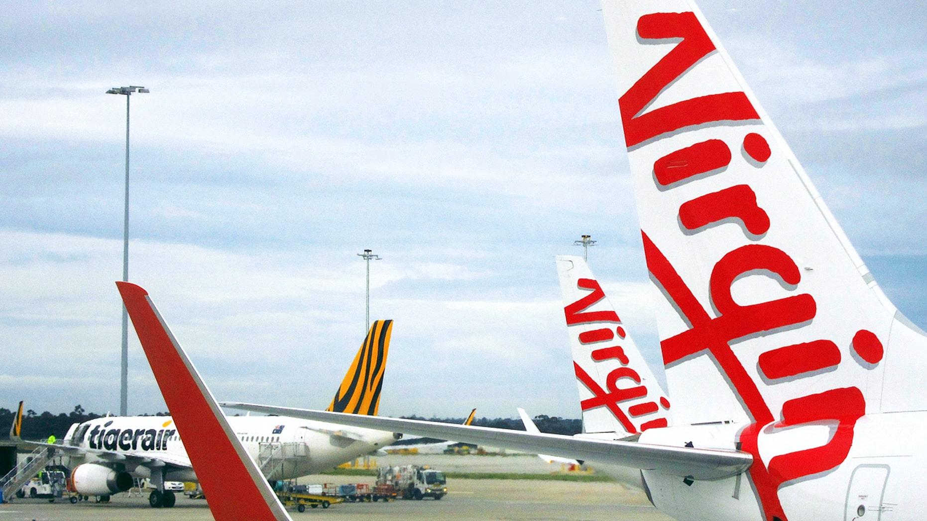 A Tigerair Australia plane sits on the tarmac near Virgin Australia aircraft at Melbourne's Tullamarine International Airport, Australia, October 12, 2016. Picture taken October 12, 2016.     REUTERS/David Gray - RTX2ZF7U