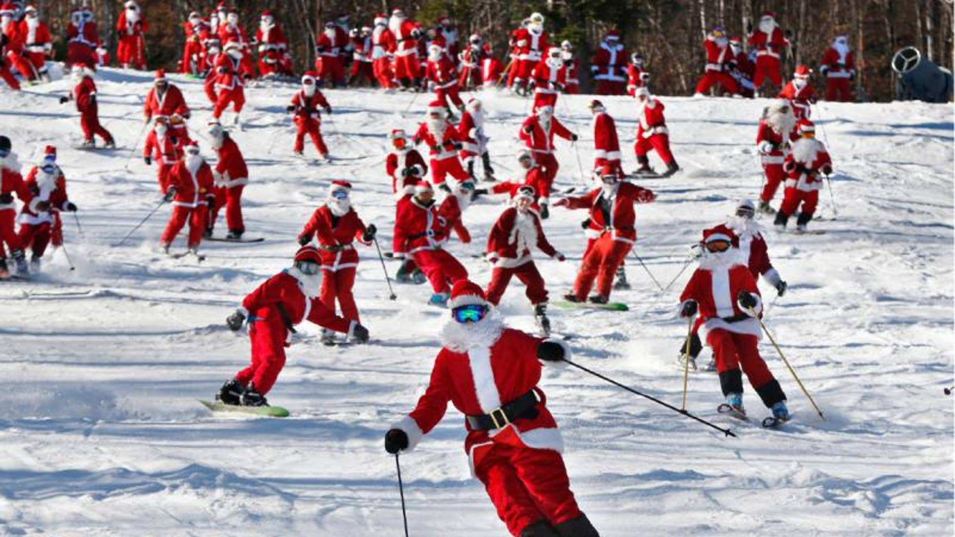 Skiers and snowboarders dressed as Santa take a run en masse at the Sunday River ski resort, Sunday, Dec. 6, 2015, in Newry, Maine. The annual Santa Sunday fundraising event raised $3,014 for the Sunday River Community Fund