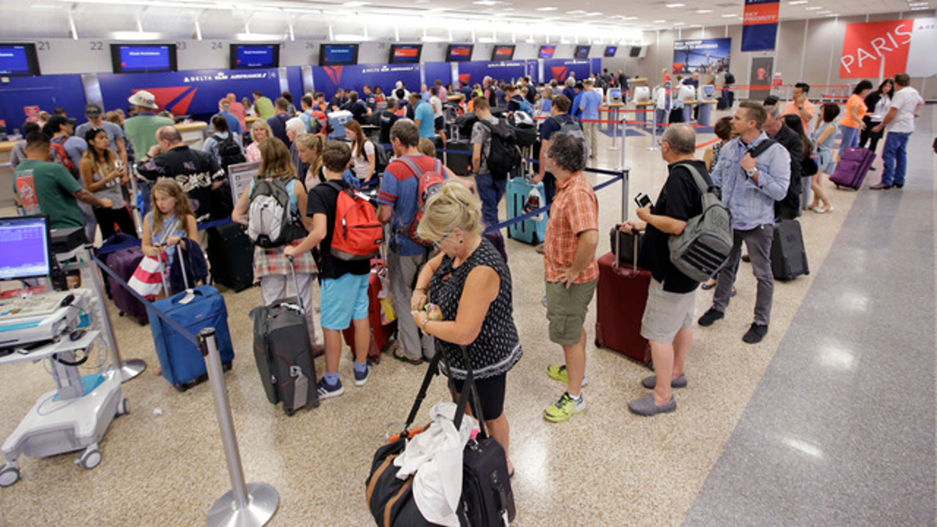 Delta Air Lines passengers stand in line after flights resumed Tuesday in Salt Lake City, Utah.