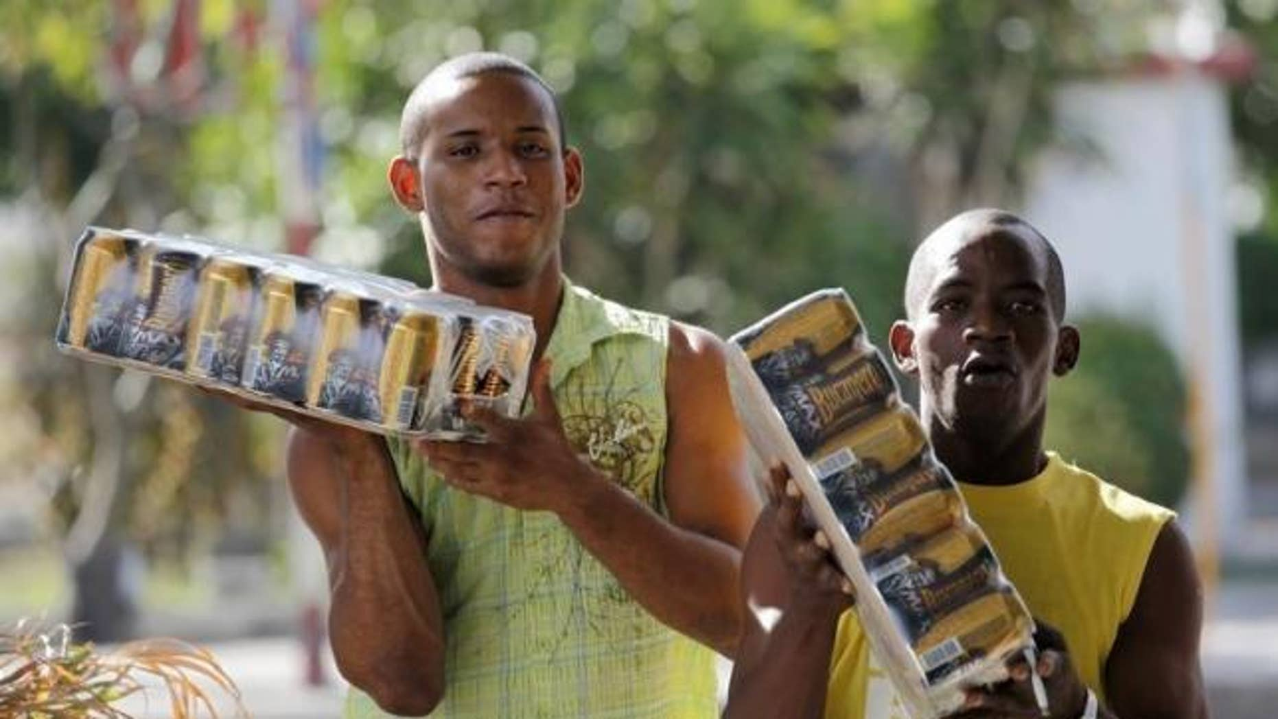 Men carry cartons of Bucanero beer in Havana, Cuba Oct. 20, 2009.