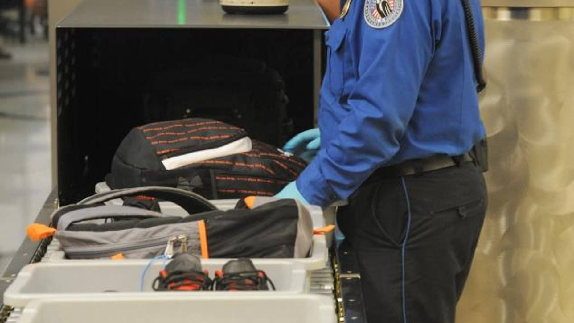A security agent guides bags through the scanner.