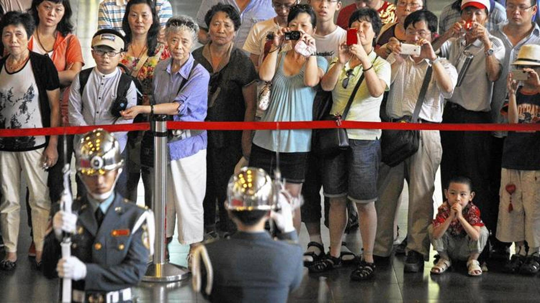 Chinese tourists take pictures of the changing of the guard at the Sun Yat-sen Memorial Hall in Taipei, Taiwan.