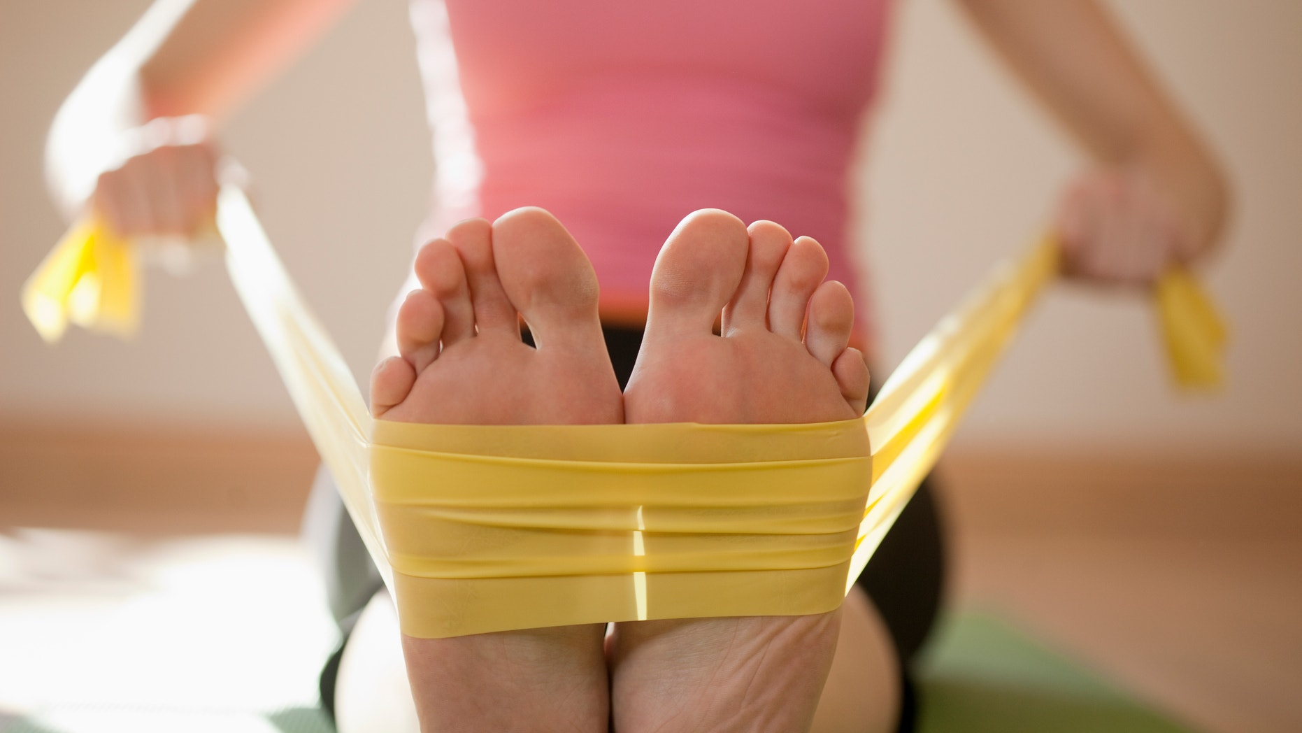 Woman exercises with resistance bands around her feet. Horizontal shot.