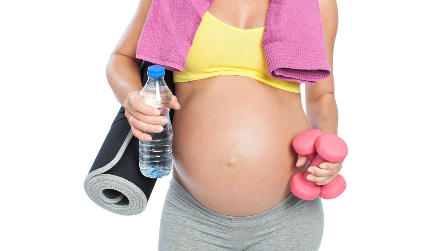 Pregnant woman standing with fitness accessories