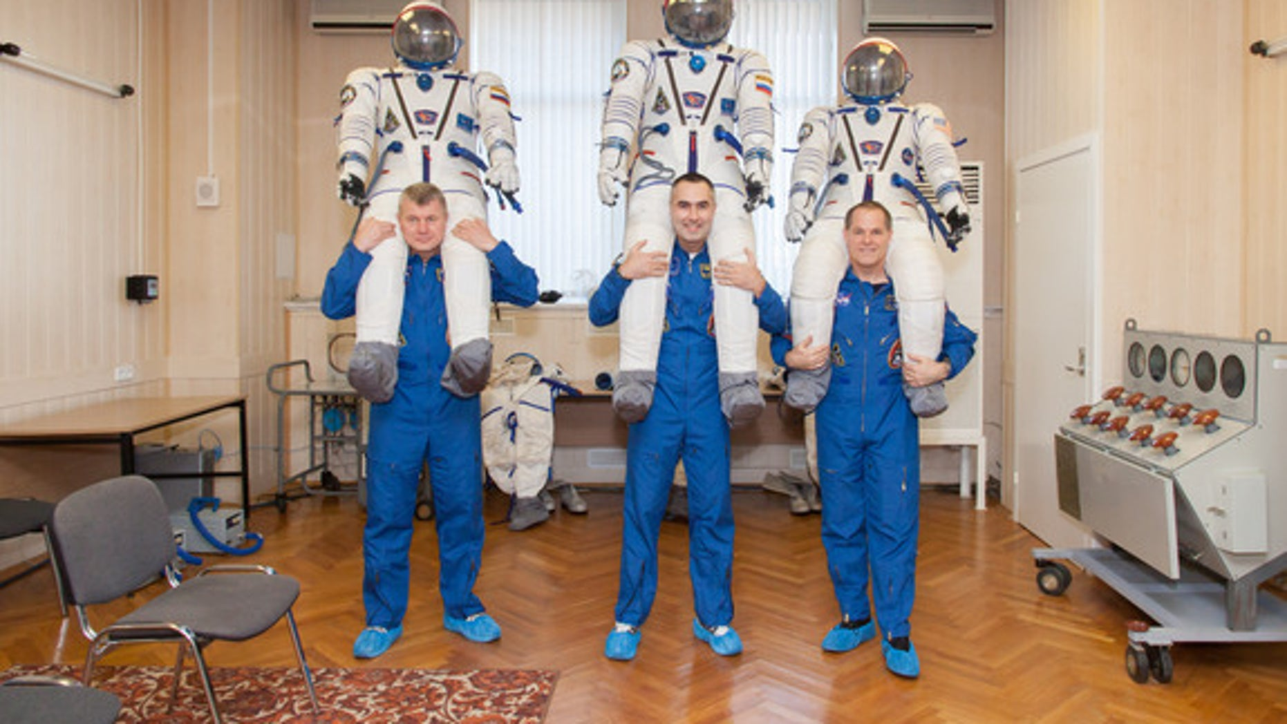 "At the Baikonur Cosmodrome in Kazakhstan, the Expedition 33 crew share a playful moment Oct. 10, 2012 during the first of two so-called ""fit check"" dress rehearsal sessions. From left to right are Soyuz Commander Oleg Novitskiy, Flight Engineer"
