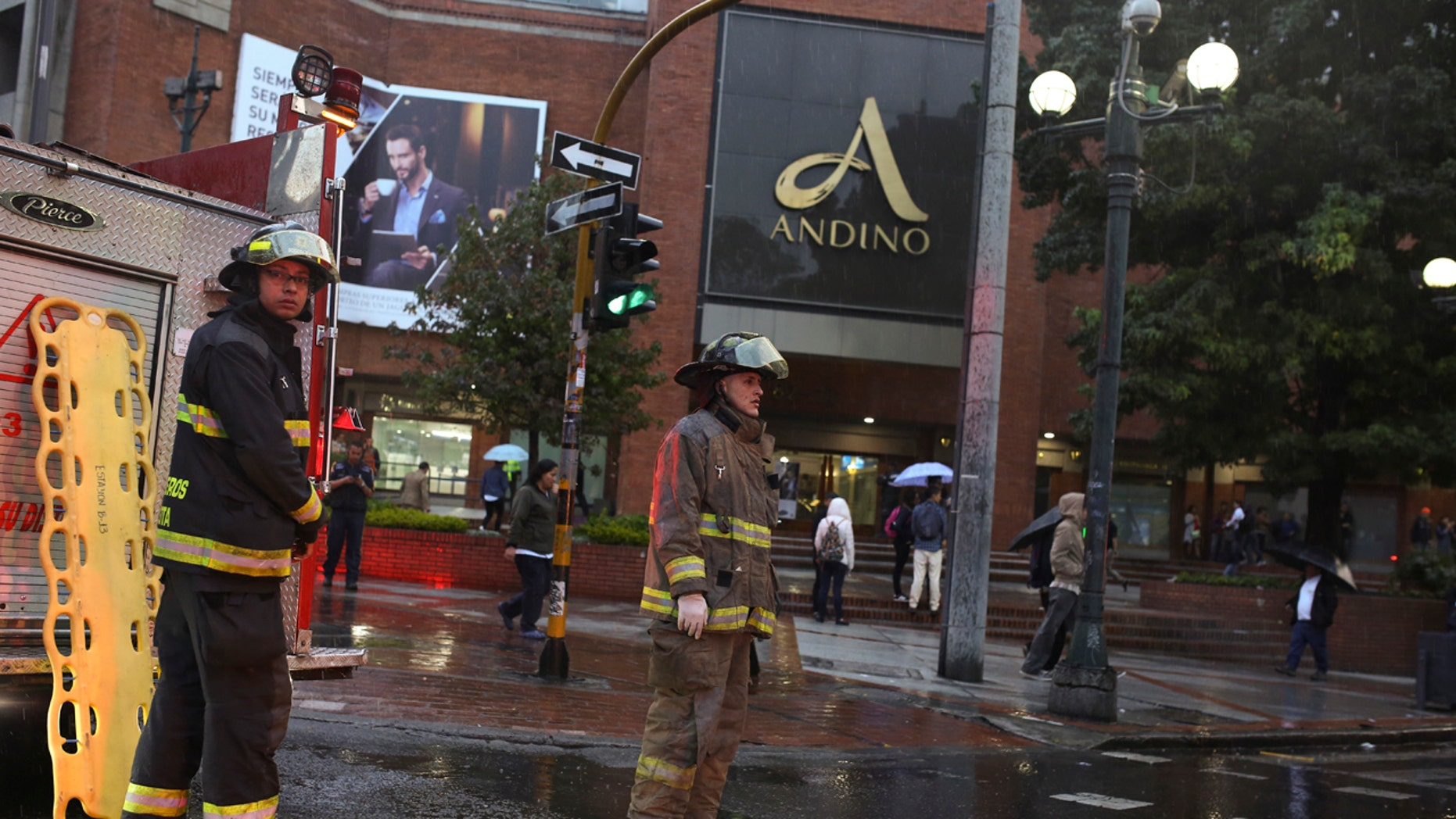 Firefighters stand outside the Centro Andino shopping center in Bogota, Colombia, Saturday, June 17, 2017.