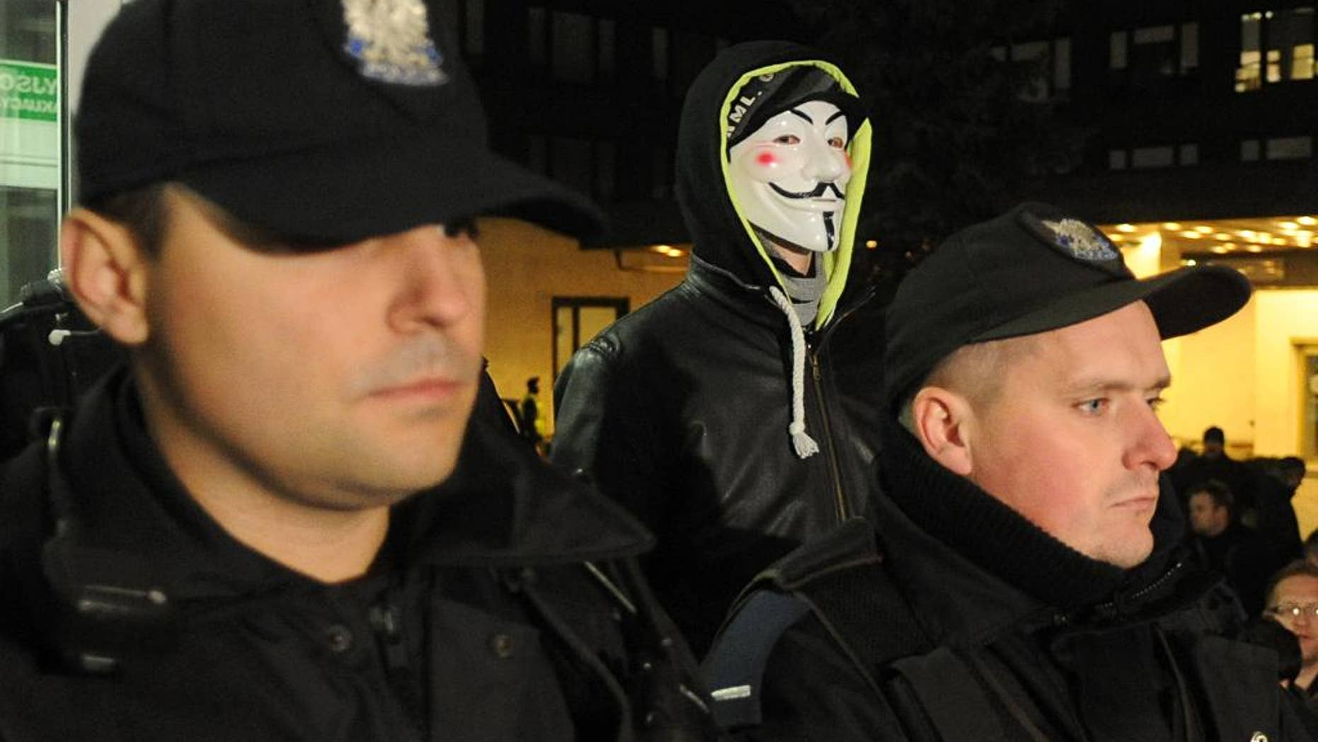 Police officers block the entrance to the National Electoral Office as a man wearing a mask stands behind, in Warsaw, Poland, Thursday, Nov. 20, 2014. Earlier a group of right wing activists entered the building and began to occupy it demanding the members of the National Electoral Office to resign. Prosecutors are investigating a hacking attack on the website of Poland's voting commission, while a top official has resigned over irregularities that are delaying the vote count in recent local elections. (AP Photo/Alik Keplicz)