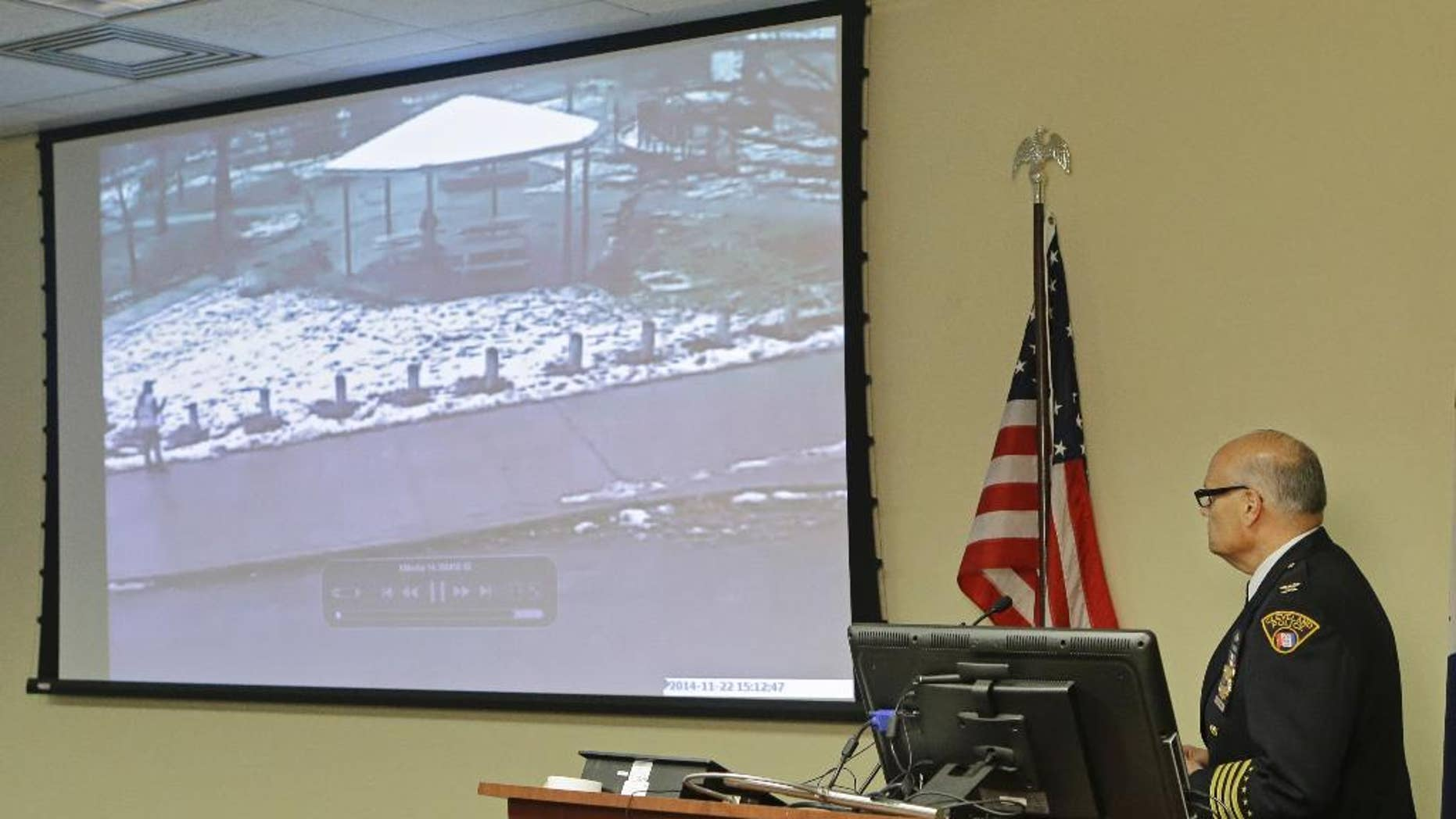 FILE- In this Nov. 26, 2014, file photo, Cleveland Police Deputy Chief Ed Tomba, right, shows surveillance video of the weekend police shooting of Tamir Rice during a news conference in Cleveland. The investigation into Rice's death is being handed over to a county sheriff's office in an attempt to make sure the probe is evenhanded, the city's mayor said Friday, Jan. 2, 2015. (AP Photo/Mark Duncan, File)