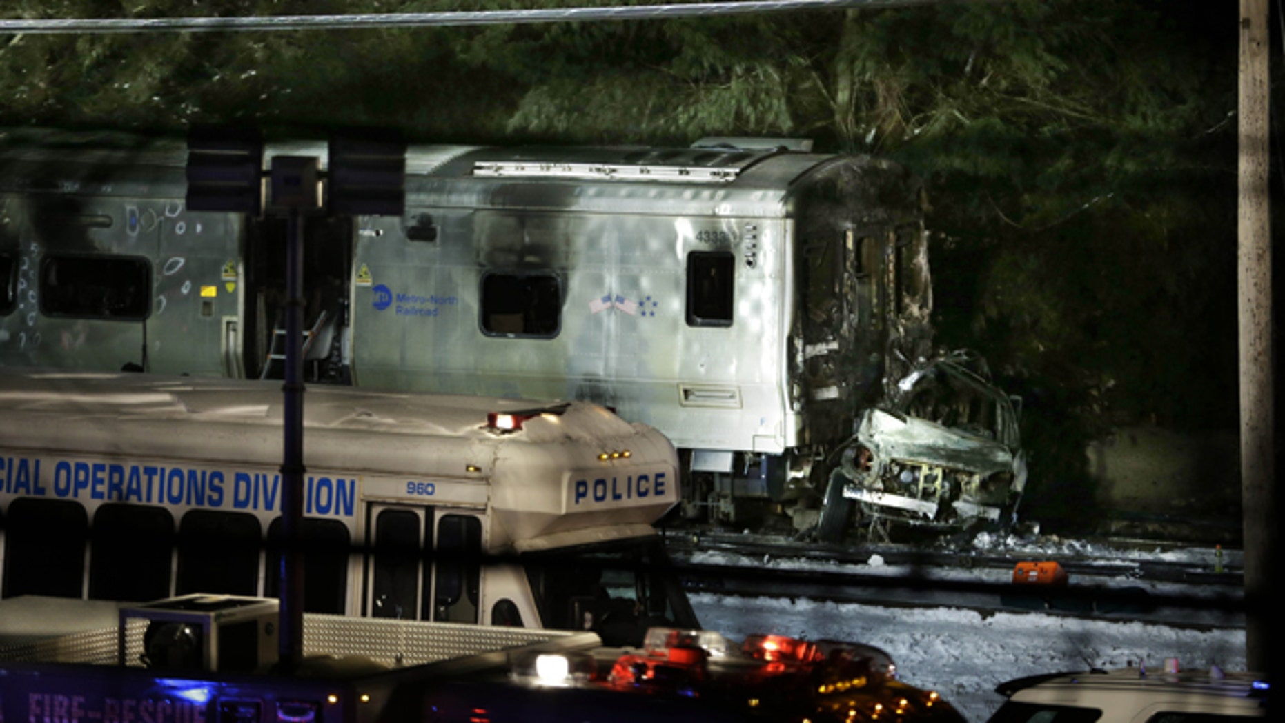 The wreckage of a car remains smashed against the front of a train in Valhalla, N.Y., Tuesday, Feb. 3, 2015. A packed commuter train slammed into a sport utility vehicle stuck on the tracks and erupted into flames Tuesday night, authorities said. (AP Photo/Seth Wenig)