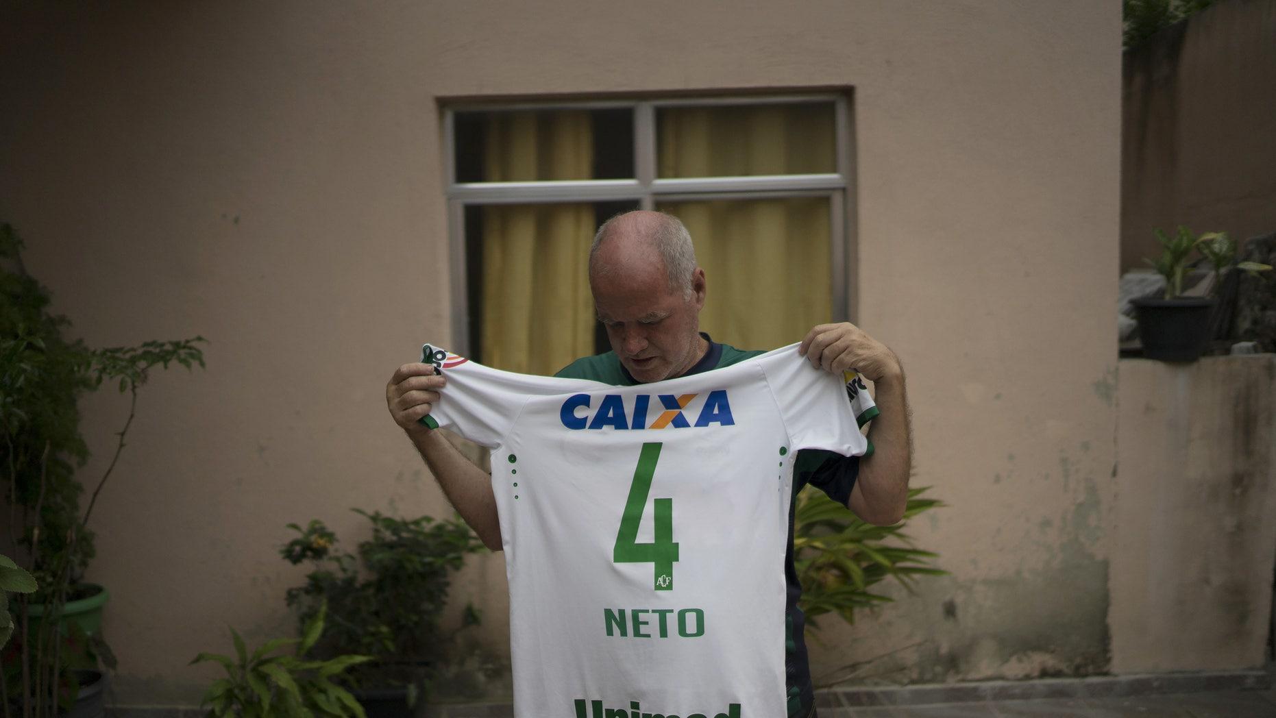 Helam Marinho Zampier Sr. shows the soccer jersey of his son Neto on Thursday, Dec. 1, 2016.