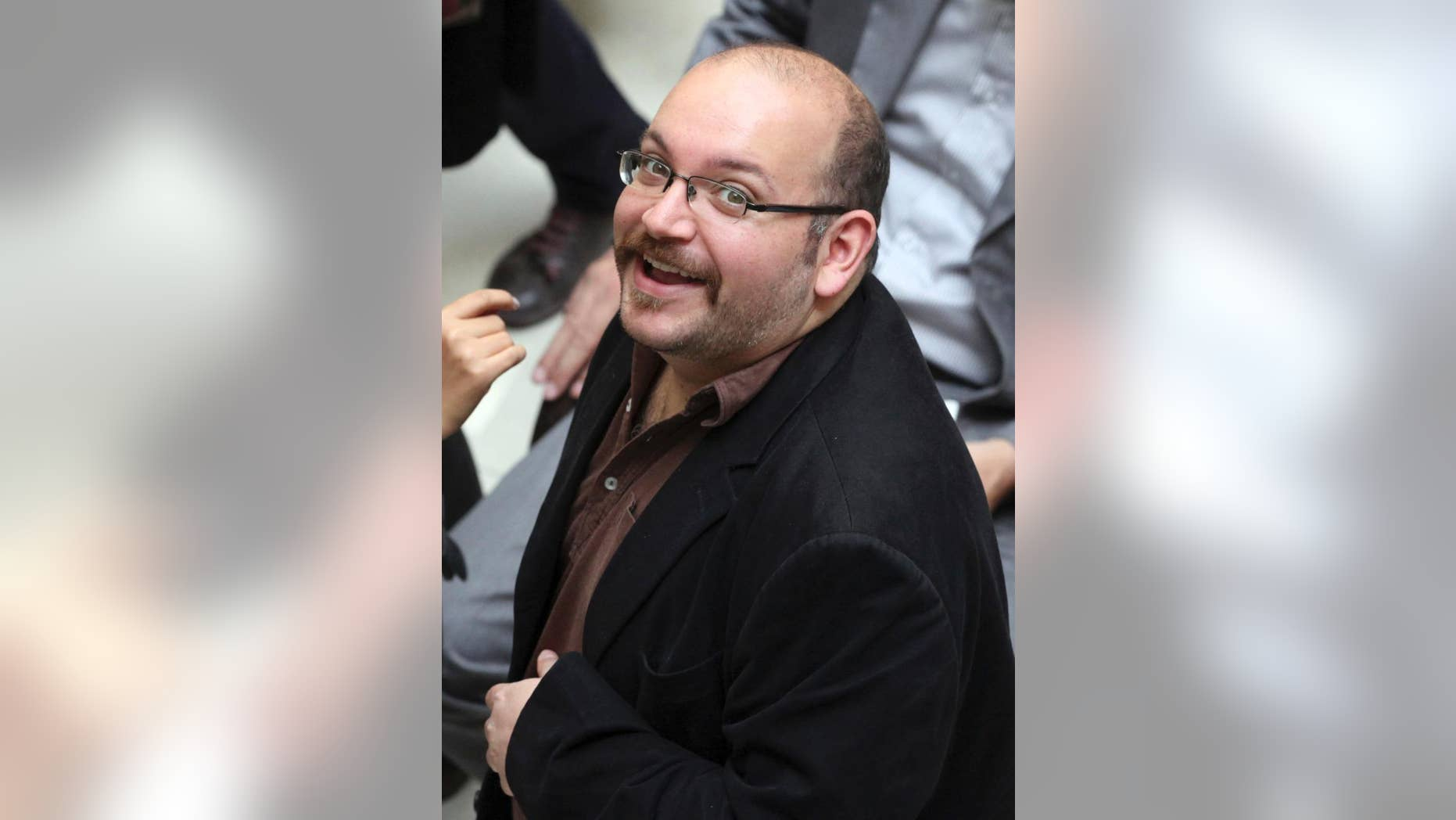 """FILE - In this photo April 11, 2013 file photo, Jason Rezaian, an Iranian-American correspondent for the Washington Post smiles as he attends a presidential campaign of President Hassan Rouhani in Tehran, Iran. The family of Rezaian jailed without charge in Iran is urging authorities in Tehran to release him, calling his incarceration a """"farce"""" 100 days after he was detained. (AP Photo/Vahid Salemi, File)"""