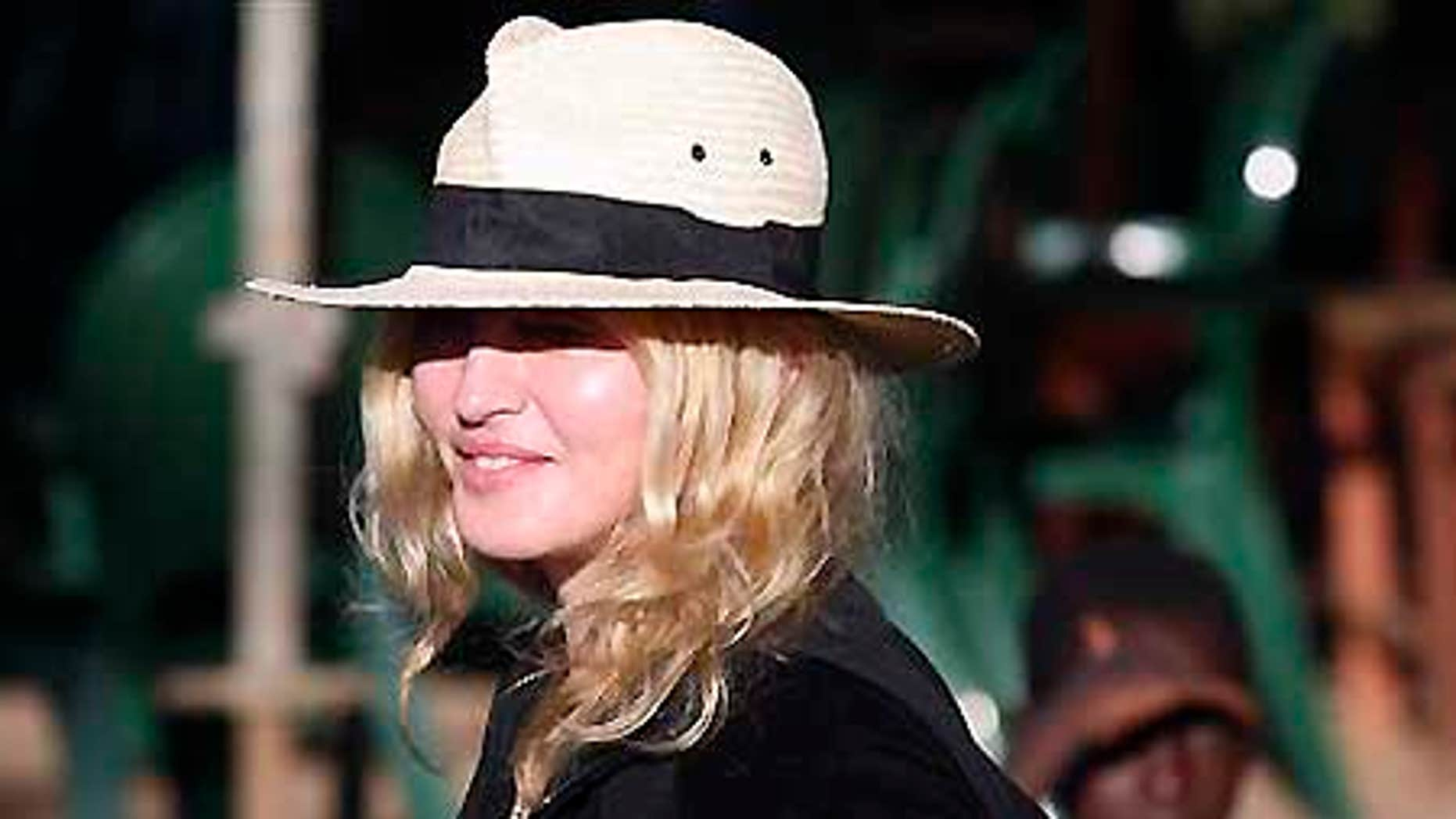 March 29, 2009: Pop star Madonna is watched by local children during a visit to Chinkhota village near Lilongwe, Malawi.