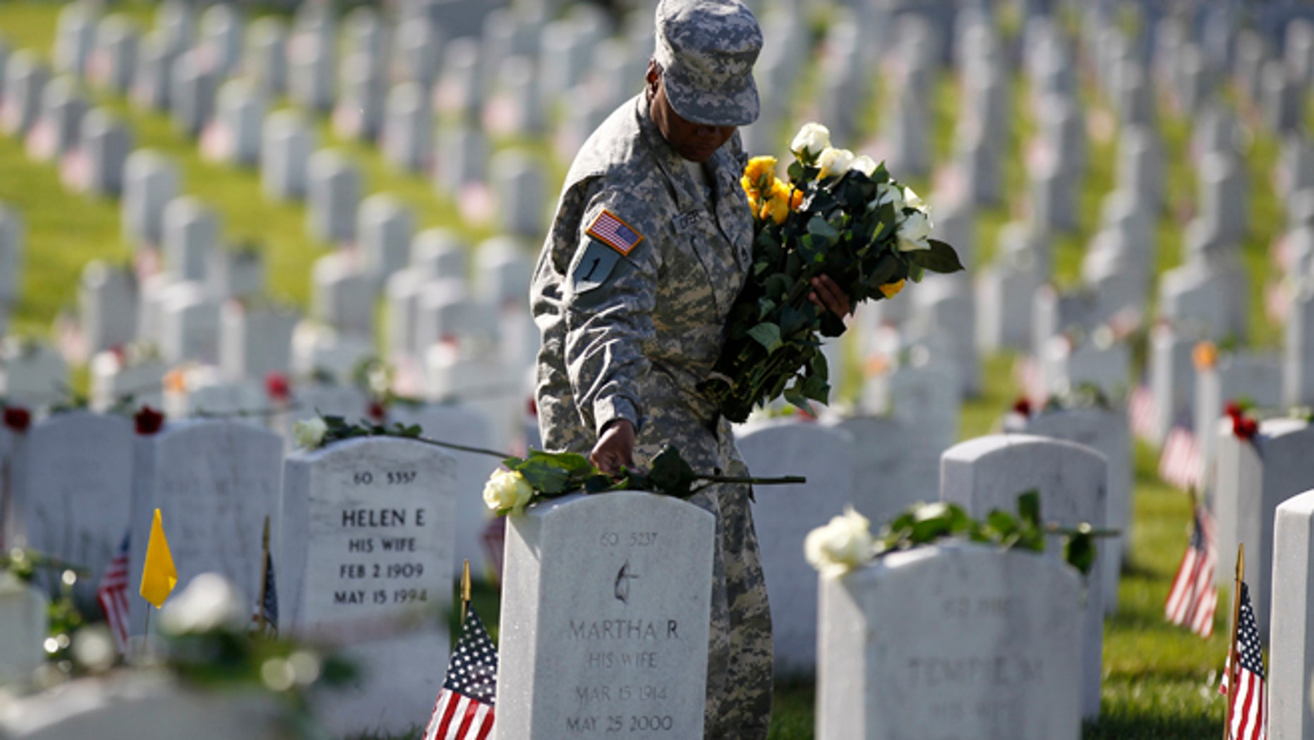 May 27, 2013: A soldier places roses on grave stones in Section 60 of Arlington National Cemetery on Memorial Day in Arlington, Va. Iraq and Afghanistan war veterans are buried in Section 60.