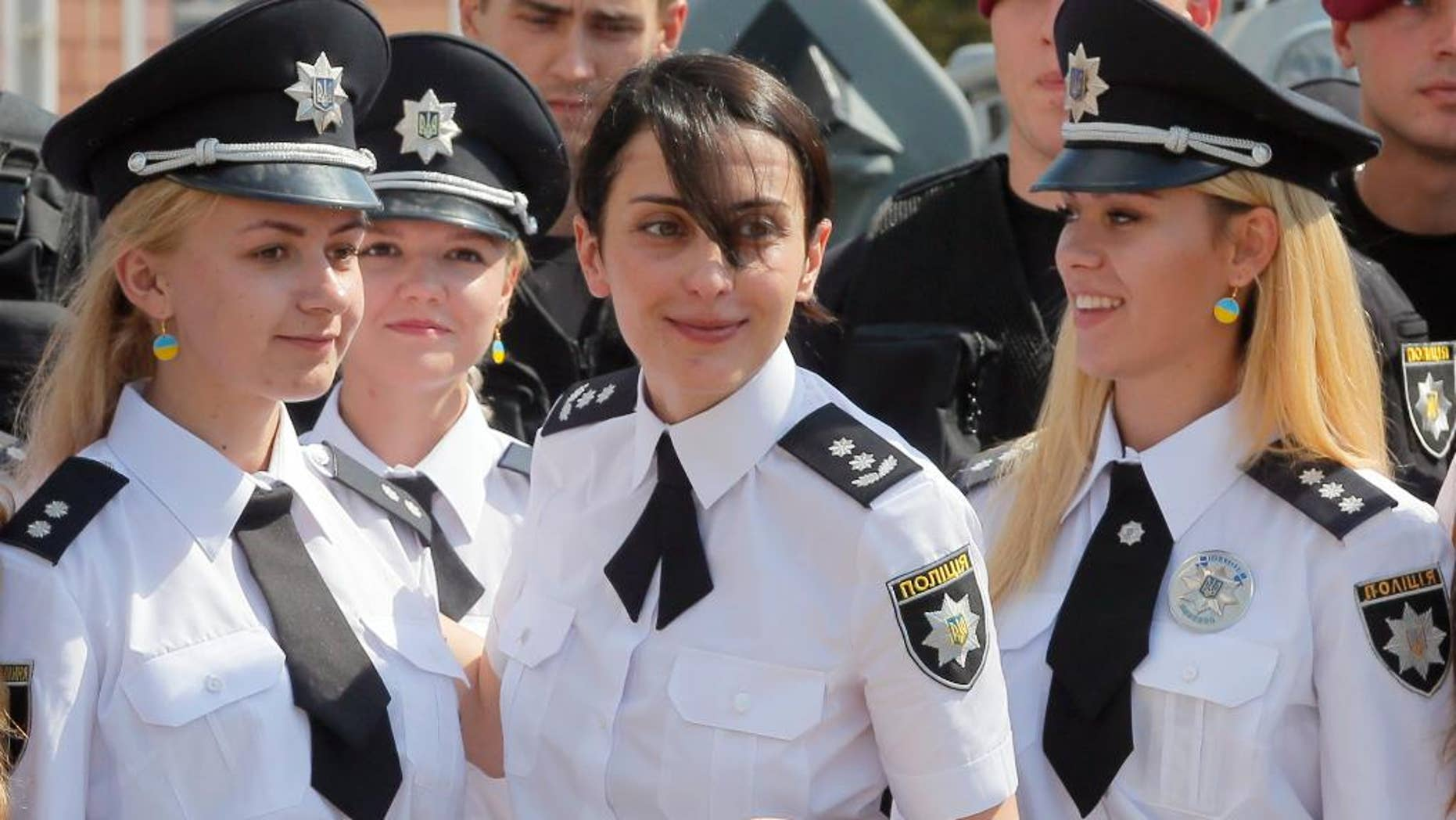 FILE In this Thursday, Aug. 4, 2016 file photo head of the National Police of Ukraine Khatiya Dekanoidze, centre, speaks with police officers during National Police Day in Kiev, Ukraine. Dekanoidze, who was driving reforms through the country's notoriously corrupt police force, has resigned Monday Nov. 14, 2016, after a year in the job, complaining of government pressure. (AP Photo/Efrem Lukatsky, File)