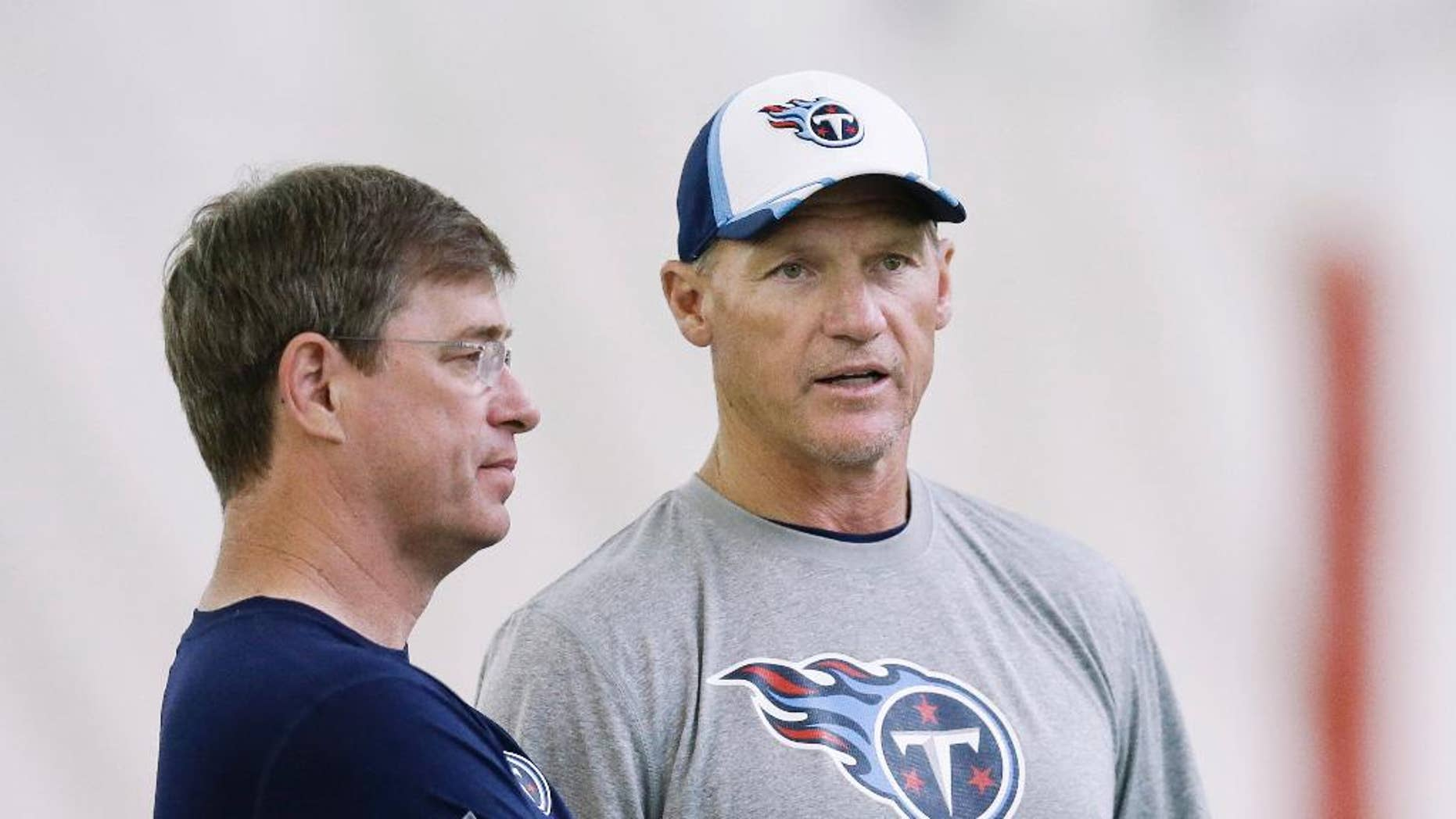 Tennessee Titans general manager Ruston Webster, left, and head coach Ken Whisenhunt talk during the NFL football minicamp on Monday, June 9, 2014, in Nashville, Tenn. (AP Photo/Mark Humphrey)