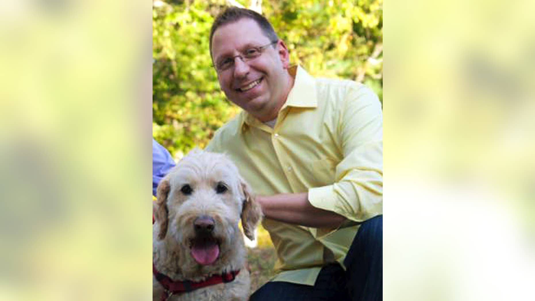 """In this Sept. 2015 photo provided by Erin X. Smithers, Michael Templeton poses with his dog in Lincoln, R.I. Templeton, 38, said he was fired from his job as music director at the Church of St. Mary in Providence, a post he held for five years, after marrying his same-sex partner. An ideological tug of war over his firing illustrates the confusion in some U.S. Roman Catholic parishes over Pope Francis' words on homosexuality. The pope's declaration """"Who am I to judge?"""" in 2013 energized Catholics who had pushed the church to accept gays and lesbians. Three years later, some gay Catholics and supporters who had hoped for rapid acceptance find themselves stymied by many bishops and pastors. (Erin X. Smithers via AP)"""