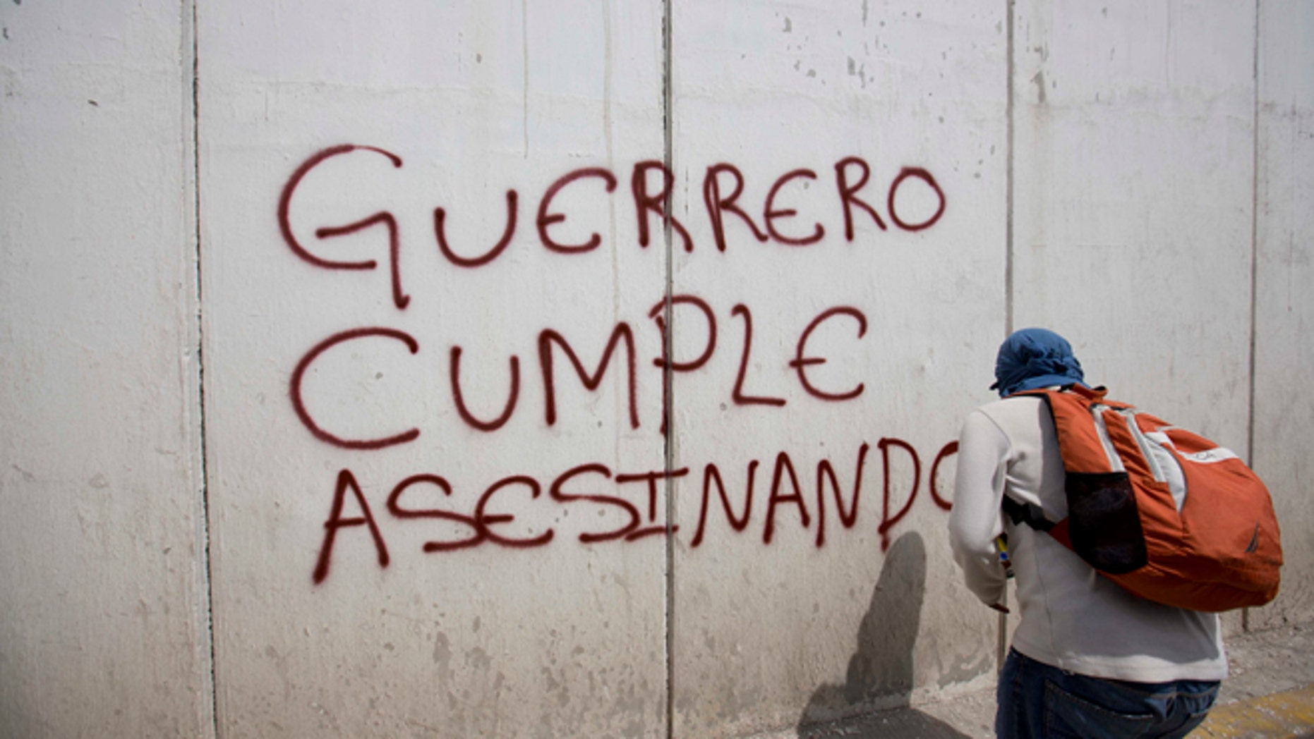 "A protester sprays a wall with the words in Spanish ""Guerrero follows through with murder"" at a demonstration against the disappearance of 43 students from the Isidro Burgos rural teachers college in Chilpancingo, in Guerrero state, Mexico, Wednesday, Oct. 8, 2014. Federal officials say they still have no explanation for violence Sept. 26 that killed six, wounded at least 25 and left so many missing. Also, investigators still had no word on whether the 28 bodies found in a mass grave last weekend included some of the missing students. (AP Photo/Eduardo Verdugo)"