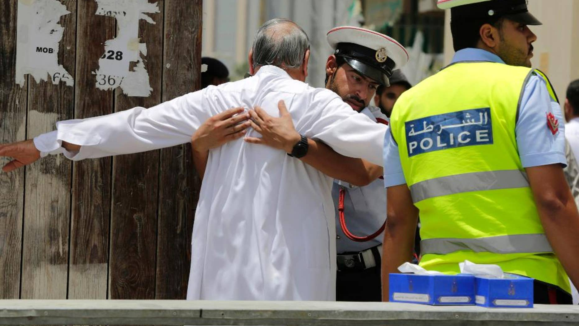 """FILE- In this Friday, June 5, 2015 file photo, Bahraini community police officers search worshipers outside a Shiite Muslim mosque ahead of mid-day prayers in Manama. Bahraini authorities say two policemen have been killed and many injured in a bomb attack south of the capital. The Interior Ministry said on its Twitter feed on Tuesday, July 28, 2015 that the officers were killed in a """"terror blast"""" in the largely Shiite community of Sitra. (AP Photo/Hasan Jamali, File)"""
