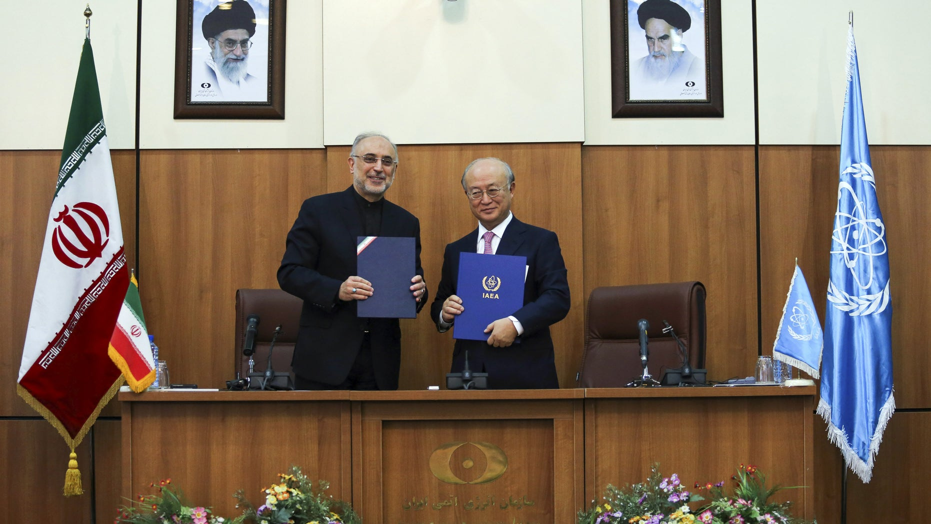 Head of Iran's Atomic Energy Organization Ali Akbar Salehi, left, and International Atomic Energy Agency (IAEA) Director General Yukiya Amano, pose for a photo under portraits of Iran's supreme leader, Ayatollah Ali Khamenei, left, and Iran's founder of Islamic Republic, Ayatollah Ruhollah Khomeini, right, following their meeting in Tehran, Iran, Monday, Nov. 11, 2013. Iran and the U.N. nuclear watchdog agency have reached a roadmap deal for cooperation during talks in Tehran Saturday that expands the monitoring of the country's nuclear sites. (AP Photo/ ISNA, Mehdi Ghasemi)