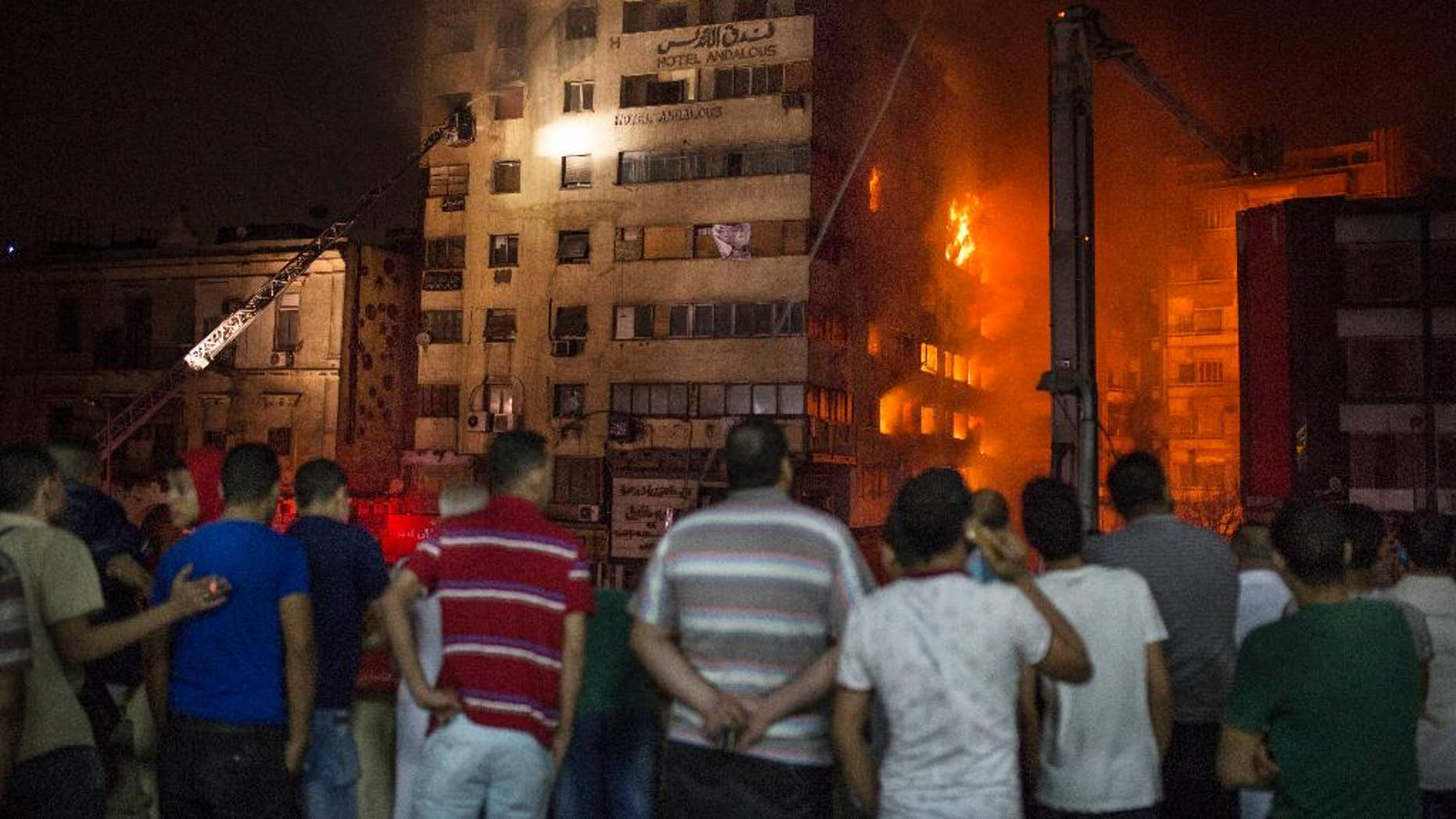 People look at a fire that erupted inside a six-story hotel called Andalusia in the populous Ataba neighborhood in Cairo, Egypt, Monday, May 9, 2016. A massive fire erupted early hours Monday morning in a busy low-price commercial area in downtown Cairo, injuring at least 60 mostly from suffocation. There were no reports of deaths. (AP Photo/Sabry Khaled)