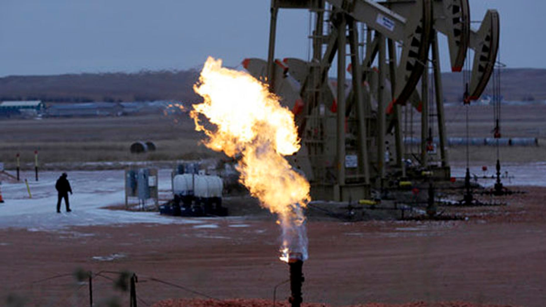Oct. 22, 2015: Workers tend to oil pump jacks behind a natural gas flare near Watford City, N.D.