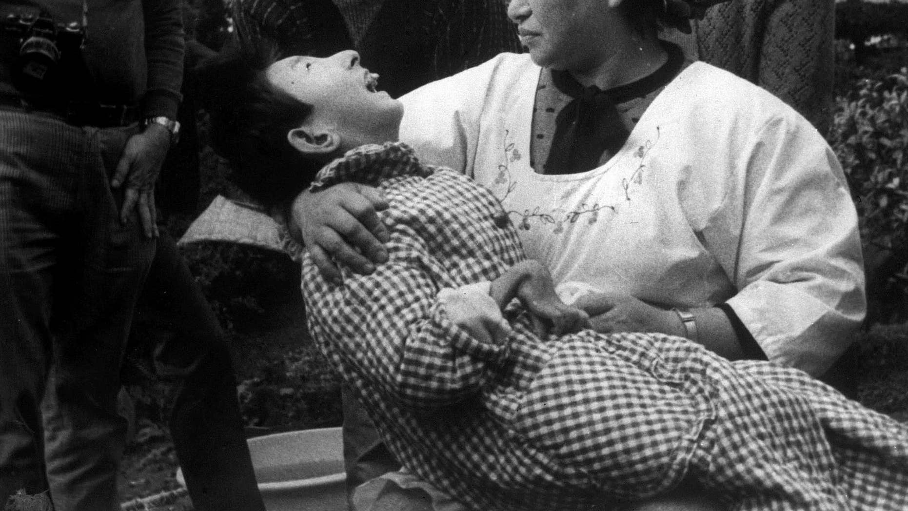 """FILE - In this 1973 photo, a woman holds a victim of """"Minamata Disease"""", or mercury poisoning, in Minamata, Japan. The girl has a malformed hand, like many victims of the disease who suffer from physical deformites among other symptoms. The Tokyo District Court has rejected a civil lawsuit demanding that tests into food toxicity and illnesses required by law be carried out for """"Minamata disease"""" poisoning. Doctor Toshihide Tsuda, who sued, said Wednesday, Dec. 7, 2016, he would appeal the court's decision. (AP Photo, File)"""