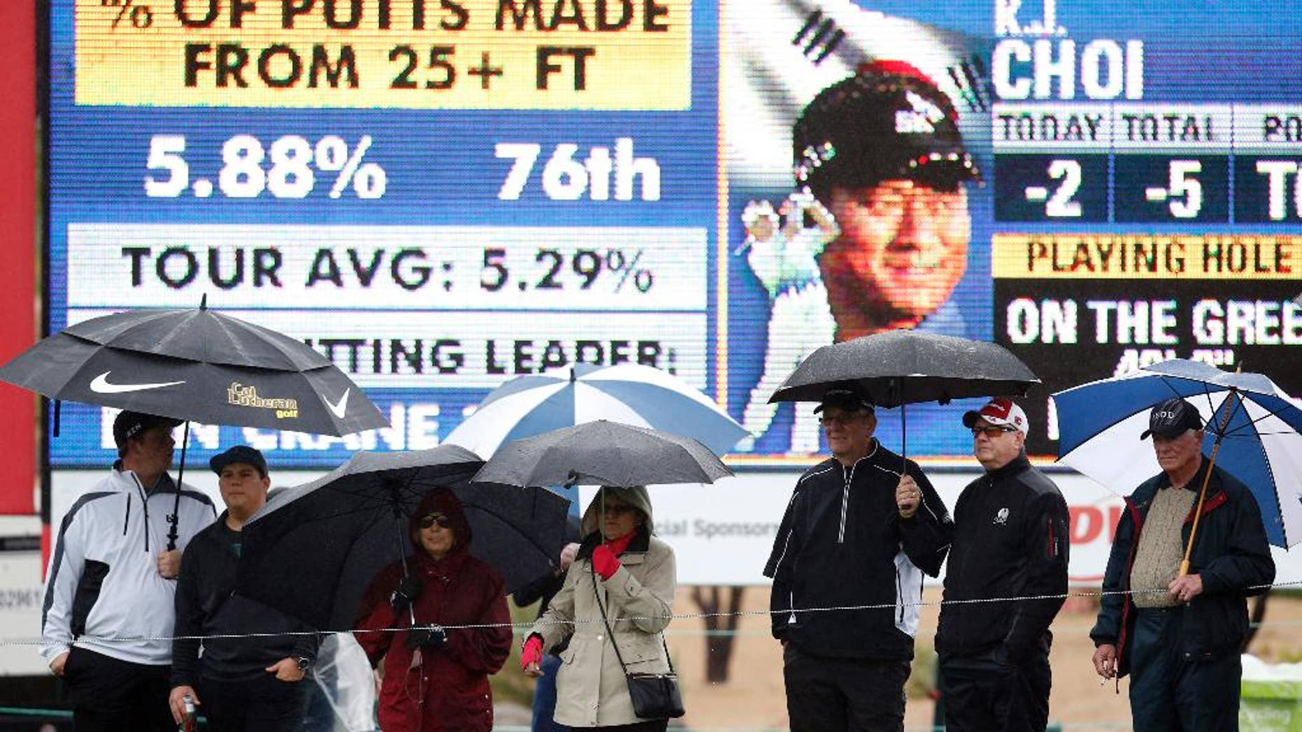 Fans, holding umbrellas, line up in front of the ninth hole during the second round of the Phoenix Open golf tournament, Friday, Jan. 30, 2015, in Scottsdale, Ariz. (AP Photo/Rick Scuteri)