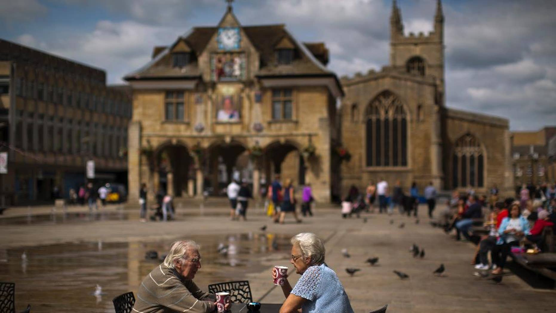 In this Wednesday, July 6, 2016 photo, a couple drink coffee in front of the Guildhall, also known as the Butter Cross, on Cathedral Square, in downtown Peterborough, East of England. Many people who voted for Britain to get out of the European Union look at multi-ethnic Peterborough as a warning example. They say British identity has been eroded in parts of the city where migrants have moved in and pubs have been replaced by shawarma shops or ethnic food stores. (AP Photo/Emilio Morenatti)
