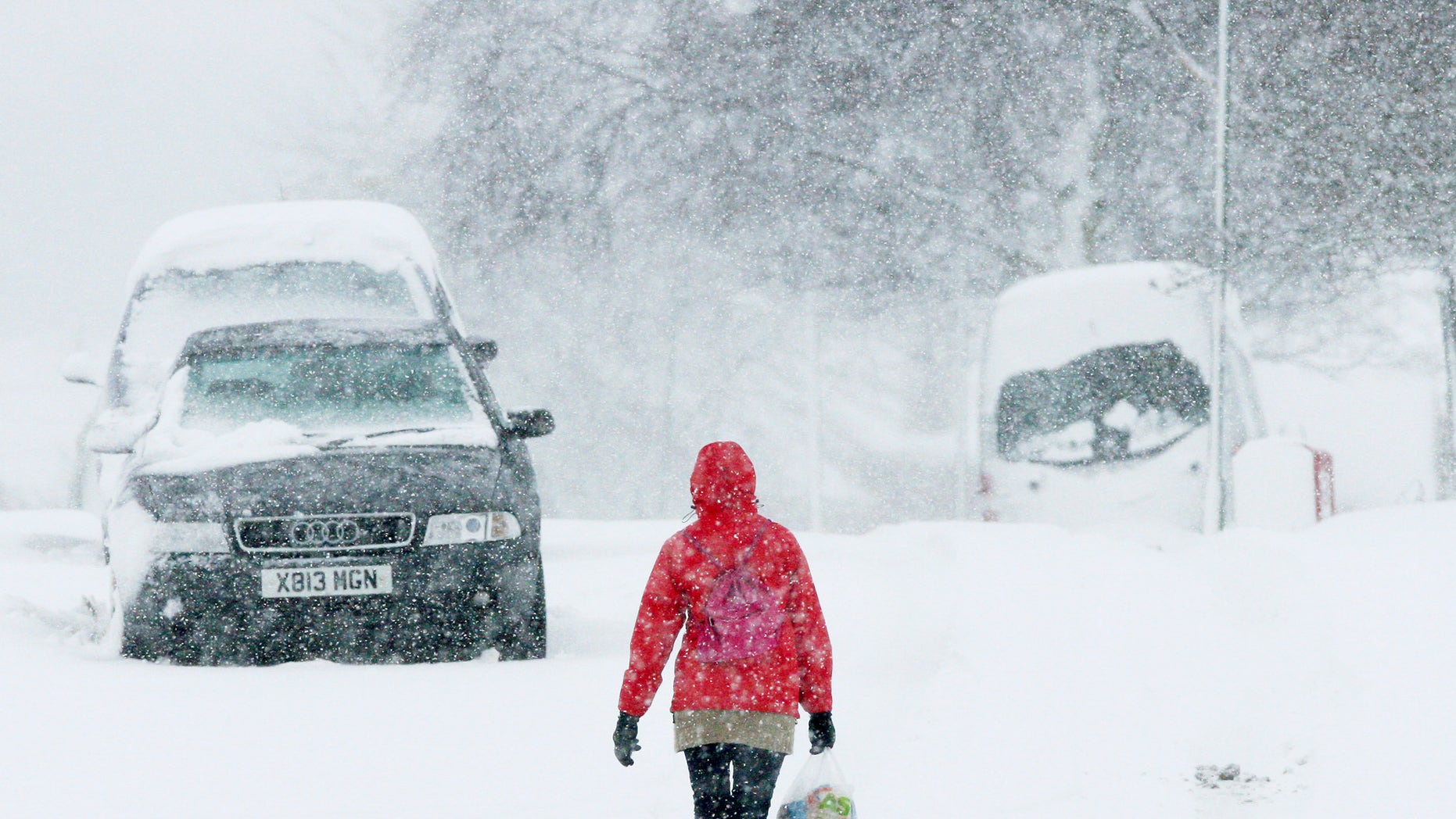 A woman walks through the heavy snow in Stanley, England, Monday, Jan. 21, 2013. The big freeze across Britain is here to stay, with more heavy snow  and falling temperatures are forecasted for Britain and Scotland. (AP Photo/Scott Heppell)