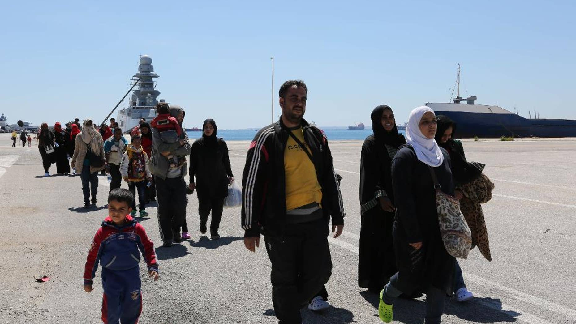 Rescued migrants walk after disembarking from an Italian Navy vessel in the harbor of Augusta, Sicily, Southern Italy, Wednesday, April 22, 2015. Italy pressed the European Union on Wednesday to devise concrete, robust steps to stop the deadly tide of migrants on smugglers' boats in the Mediterranean, including setting up refugee camps in countries bordering Libya. Italian Defense Minister Roberta Pinotti also said human traffickers must be targeted with military intervention. (AP Photo/Francesco Malavolta)