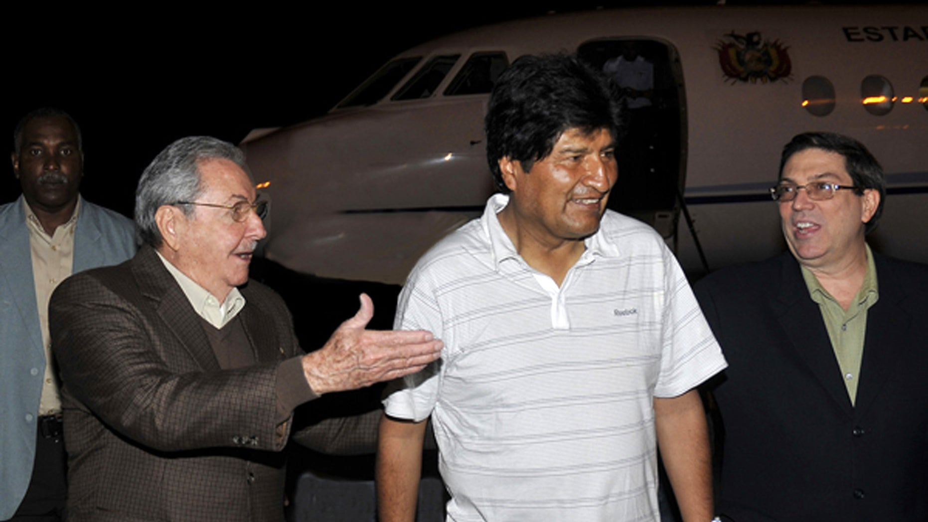In this picture released by the Cuban newspaper Juventud Revelde, Bolivia's President Evo Morales, center, is welcomed by Cuba's President Raul Castro, left, and Cuba's Foreign Minister Bruno Rodriguez at the Jose Marti international airport  in Havana, Cuba, early Sunday, Dec. 23, 2012. Evo Morales is in Cuba to visit Venezuela's President Hugo Chavez, who is recovering from a surgery, his fourth operation related to his pelvic cancer since June 2011. (AP Photo/Juventud Revelde, Estudios Revolucion)